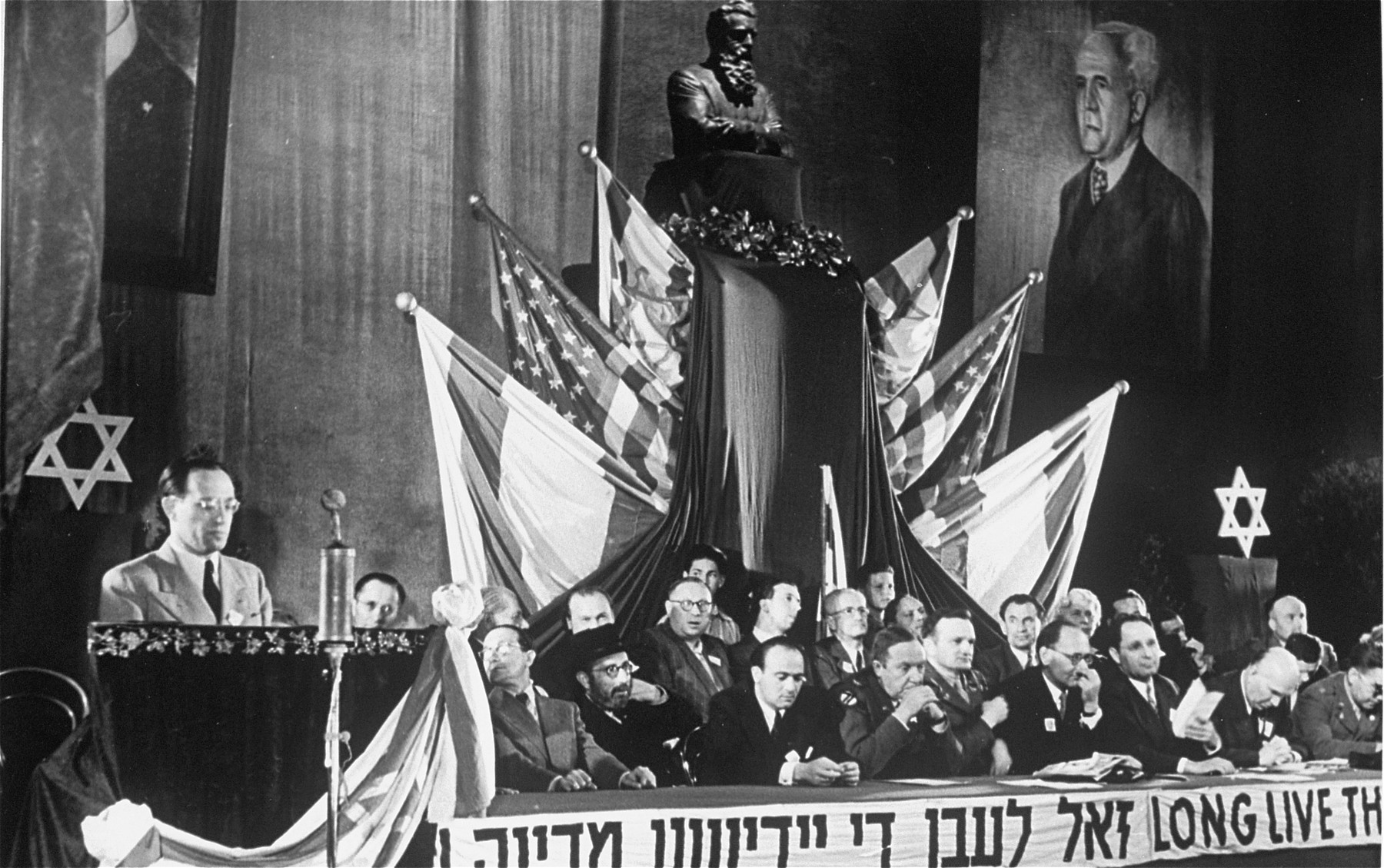 """A meeting of the Central Committee of Liberated Jews in the U.S. Zone of Germany celebrates the establishment of the State of Israel.  The banner beneath the dias reads, """"Long live the Jewish State."""""""