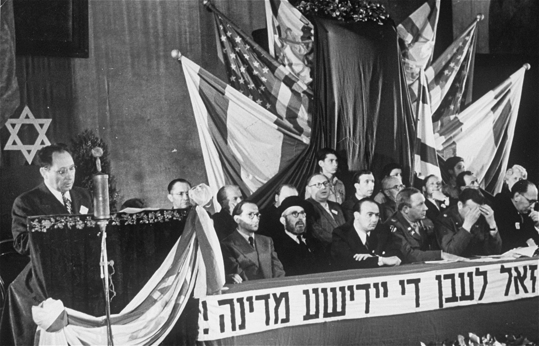 "A meeting of the Central Committee of Liberated Jews in the U.S. Zone of Germany celebrates the establishment of the State of Israel.  The banner beneath the dias reads, ""Long live the Jewish State."""