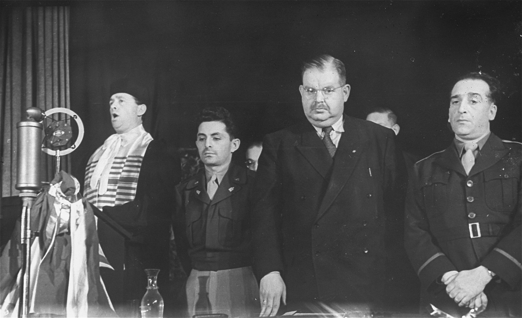 A cantor sings at a public ceremony sponsored by the Central Committee of Liberated Jews in the U.S. Zone of Germany.    Among those pictured is U.S. Army chaplain Abraham Klausner (second from the left) and Philipp Auerbach (second from the right).