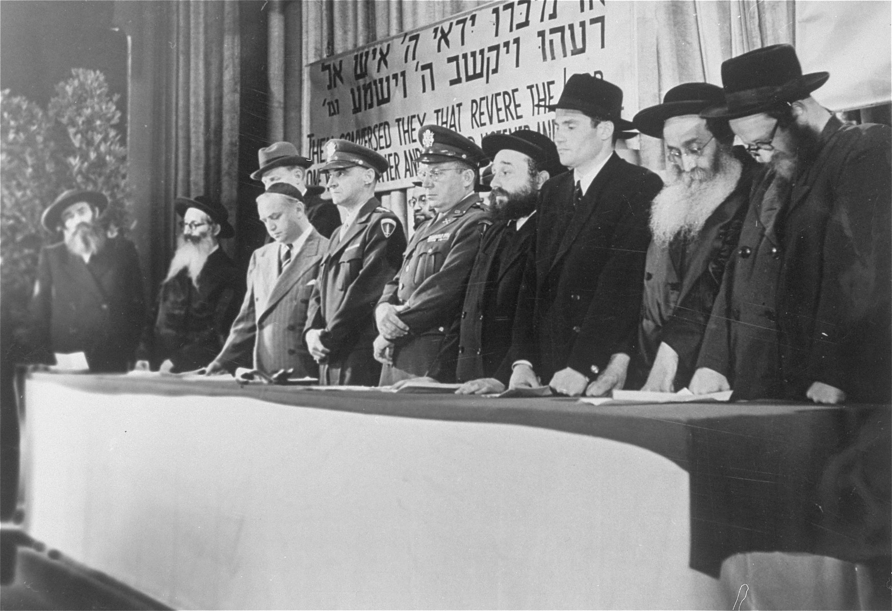 American military officers stand at the dais with a group of orthodox rabbis at a DP conference in Frankfurt.