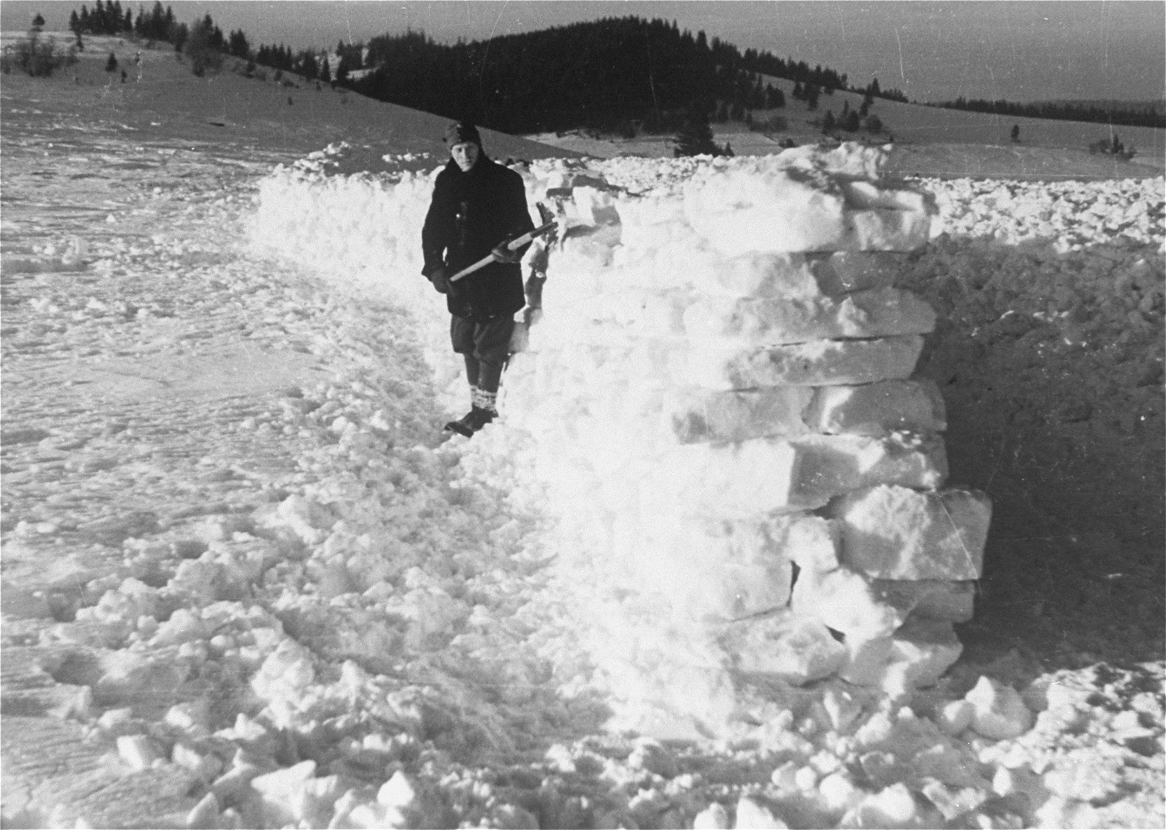 A Jewish conscript, in Company 108/57 of the Hungarian Labor Service, at forced labor constructing a barricade to prevent snow from drifting onto a road.
