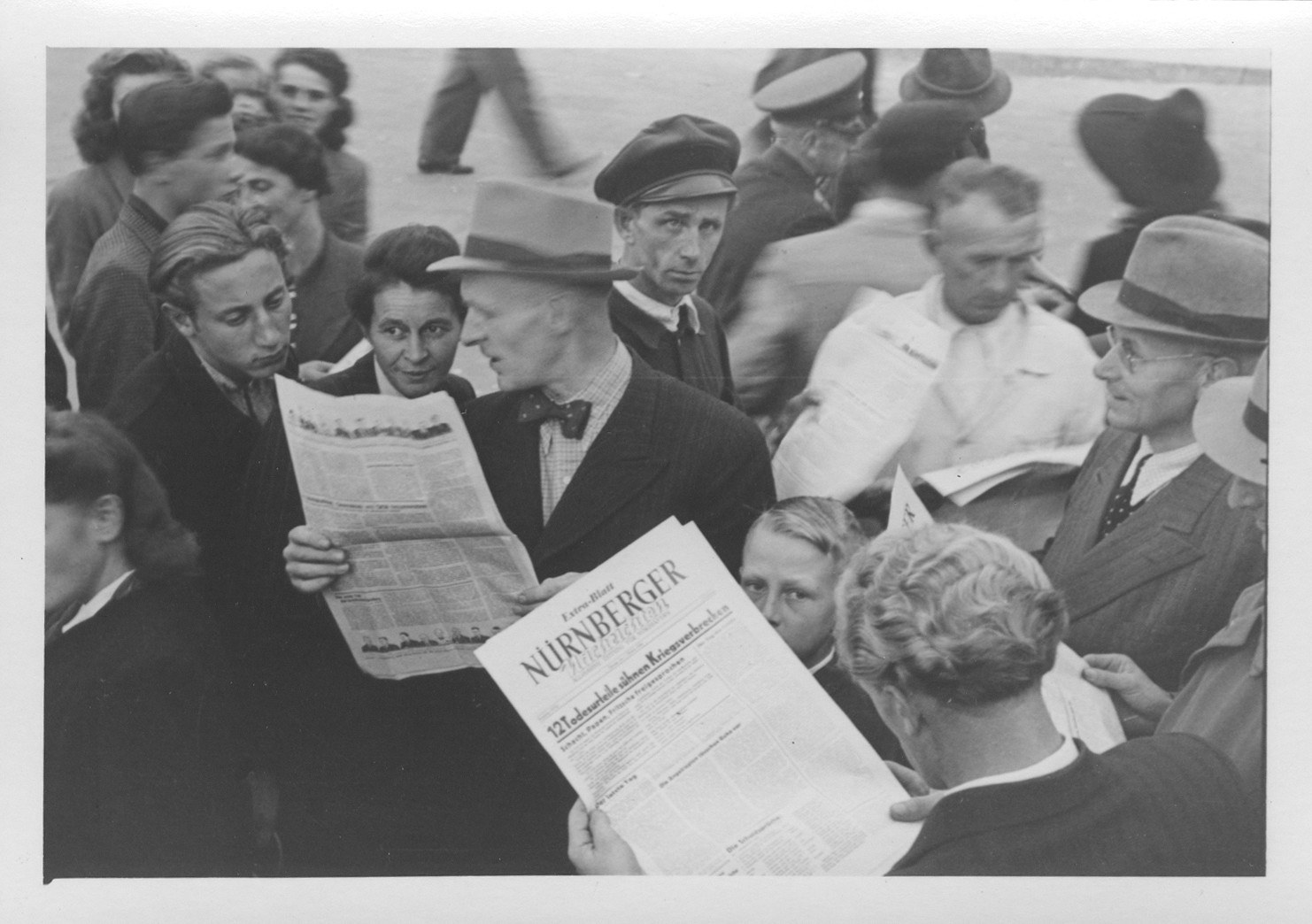 A crowd eagerly reads the special edition of the Nurnberger newspaper reporting on the sentences meted out by the International Military Tribunal.