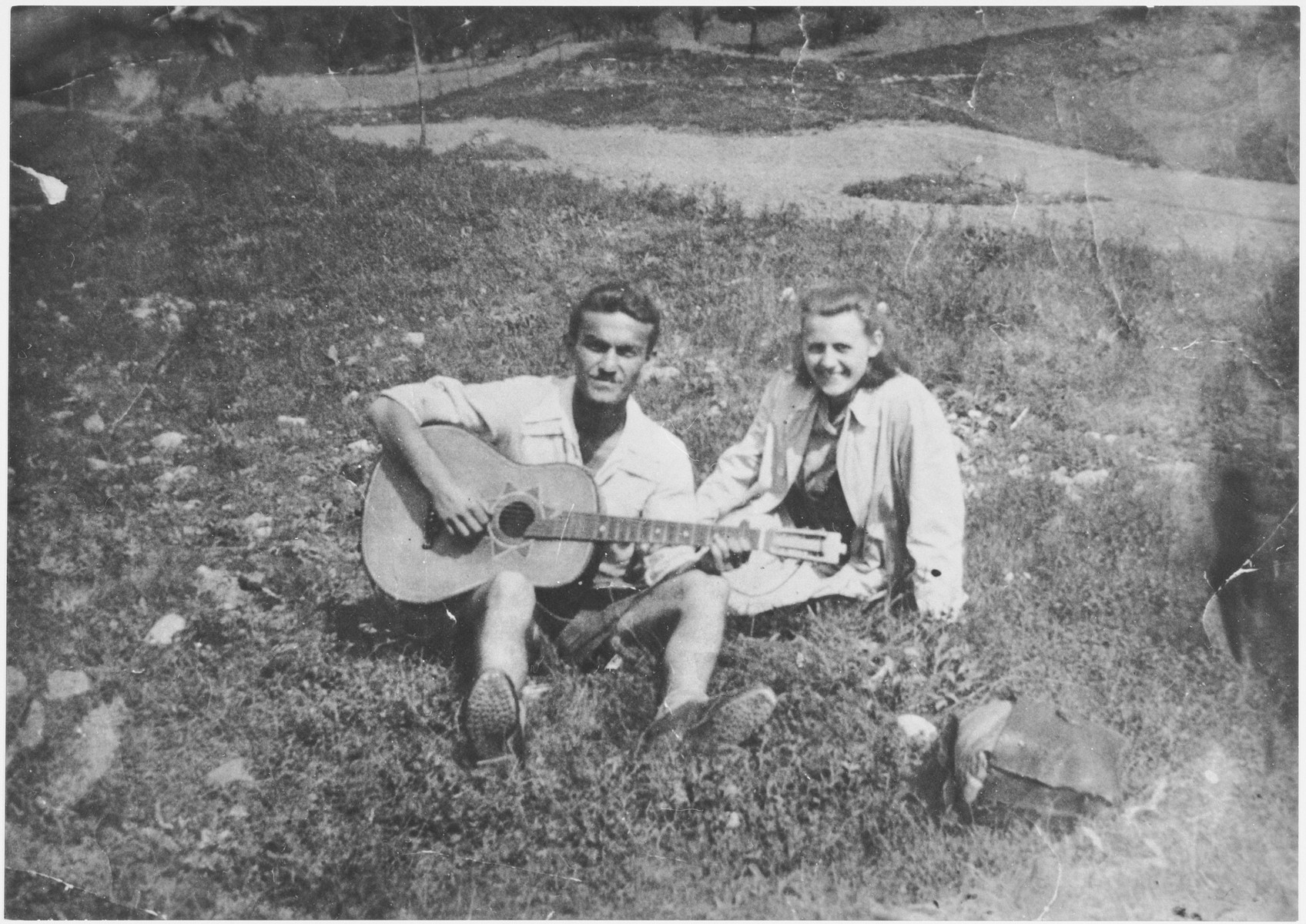 A Bosnian youth plays guitar for his girlfreind while sitting in an open field.  Pictured are Slavko Stolic and his girlfriend Angelina Ditrik. Slavko Stolic was an iron-monger in the Bosnian town of Zenica.  He was arrested there on December 8, 1944 and deported to the Jasenovac concentration camp one week later.  He was killed there in April 1945. Angelina Ditrik was also killed in Jasenovac, along with her two sisters.
