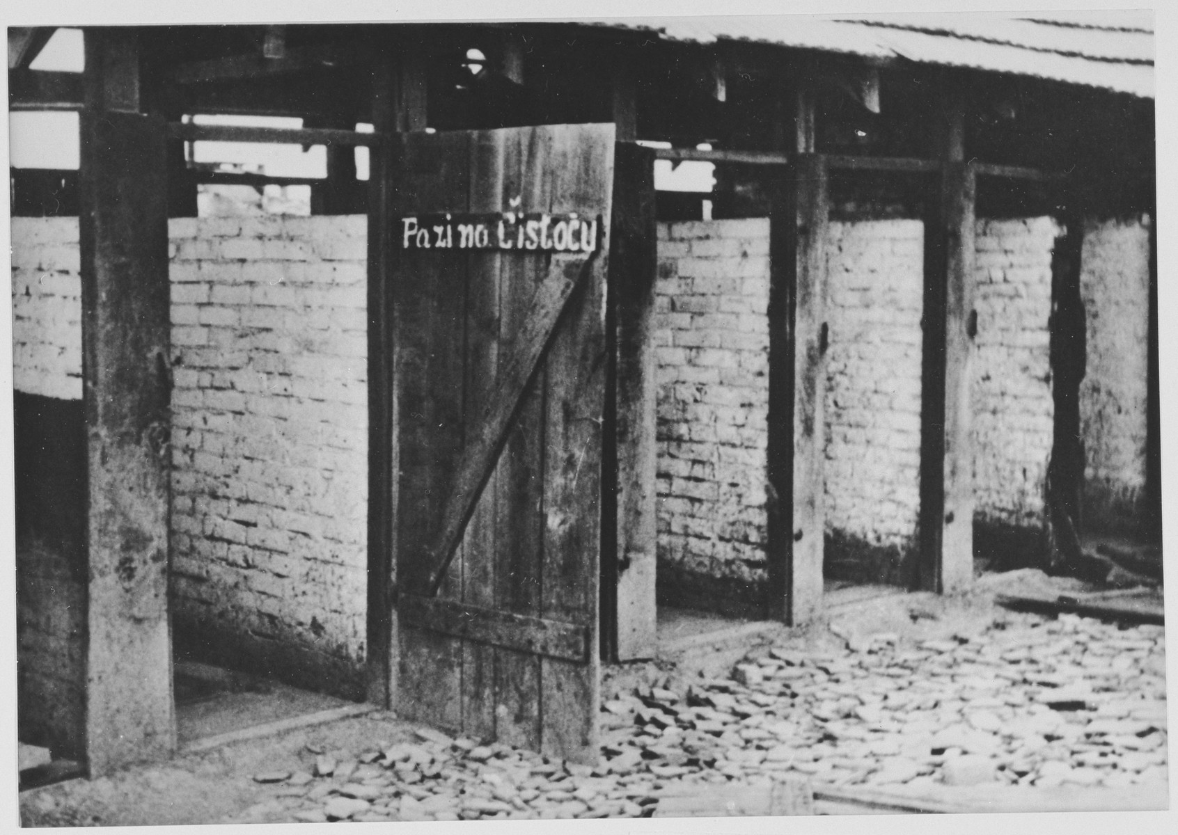 """View of the latrines in the Jasenovac concentration camp. The sign on the door reads, """"Be aware of cleanliness."""""""