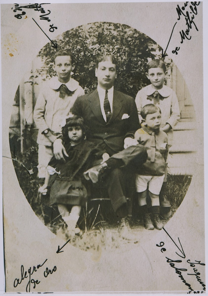 Portrait of a Jewish family sitting outside.  Pictured in the front row are Allegra Franko, Dario Nehama (seated), and Isaac Nehama (son of Solomon Nehama).  Standing in the back are Egisto Aroesti and Moise Aroesti.