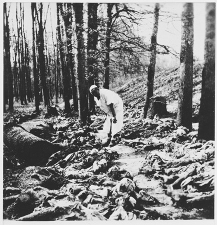 A Yugoslav war crimes investigator (named Rodic) examines exhumed bodies in the Uskoci Forest.