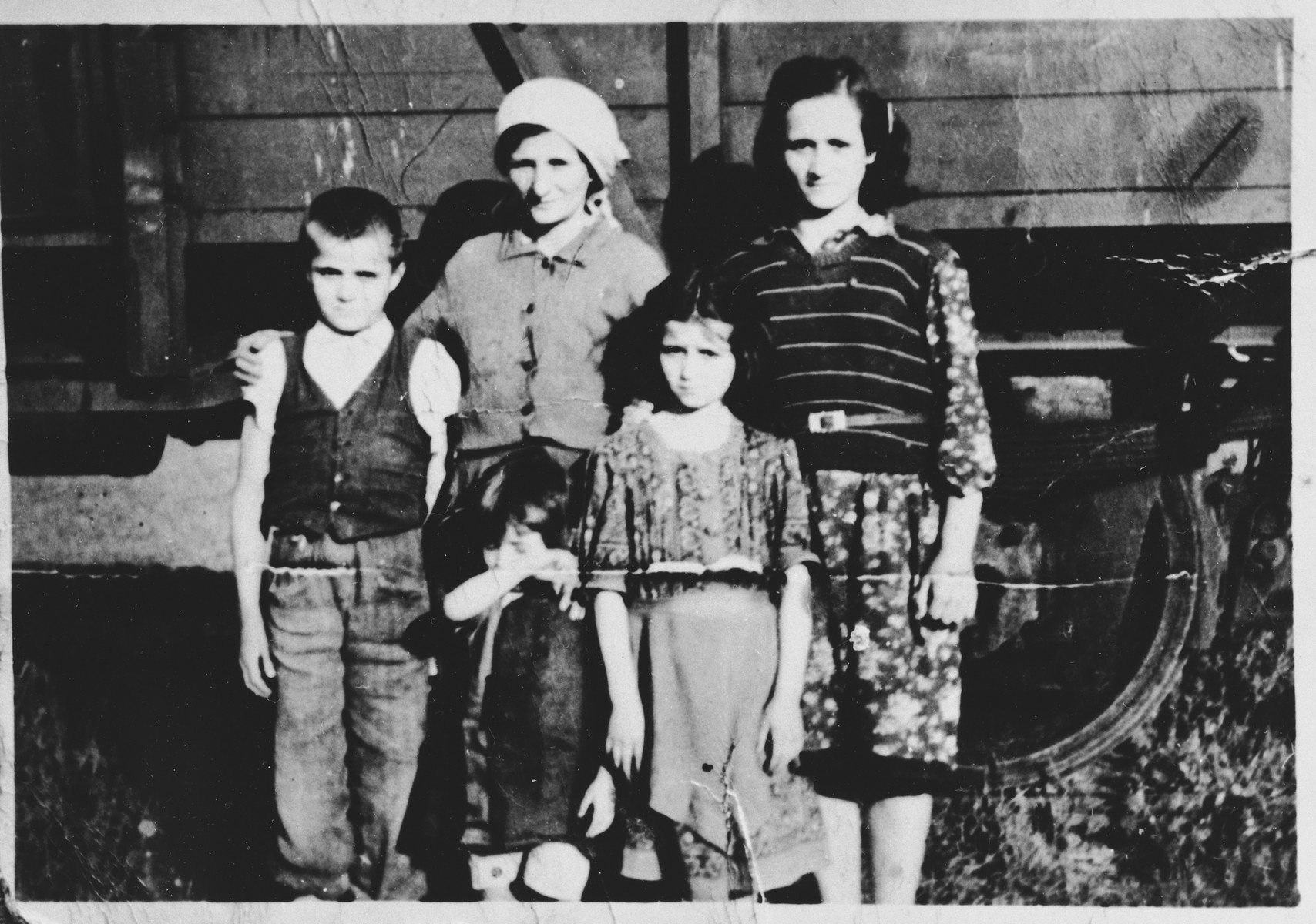 Members of a Serbian family pose in front of a railcar in the Pecana camp in Sisak.  The family is from the village of Gornje Dubrave in the district of Ogulin.  Pictured are: Staka Visnjic (b. 1903), Milica (b. 1926), Nikola (b. 1931), Ankica (b. 1932), and Mara (b. 1939).