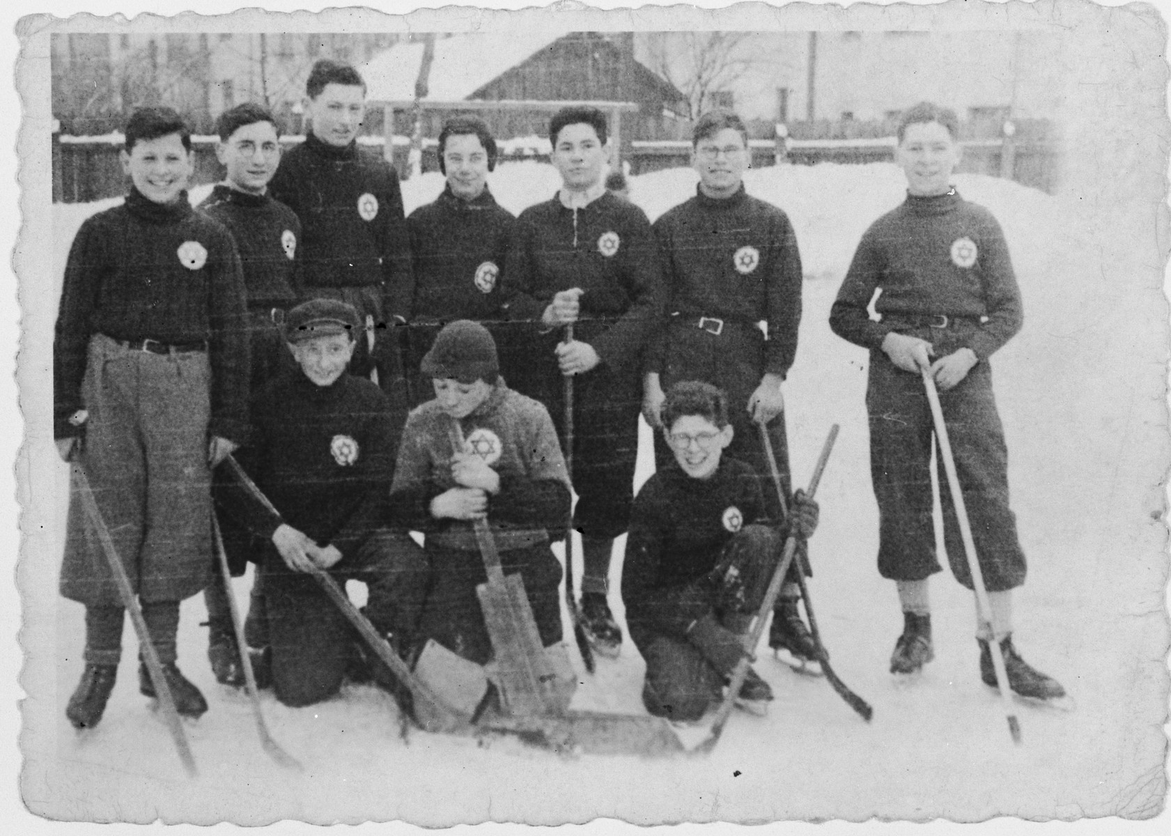 Members of a Jewish ice hockey team wearing stars of David on their shirts pose in the snow.