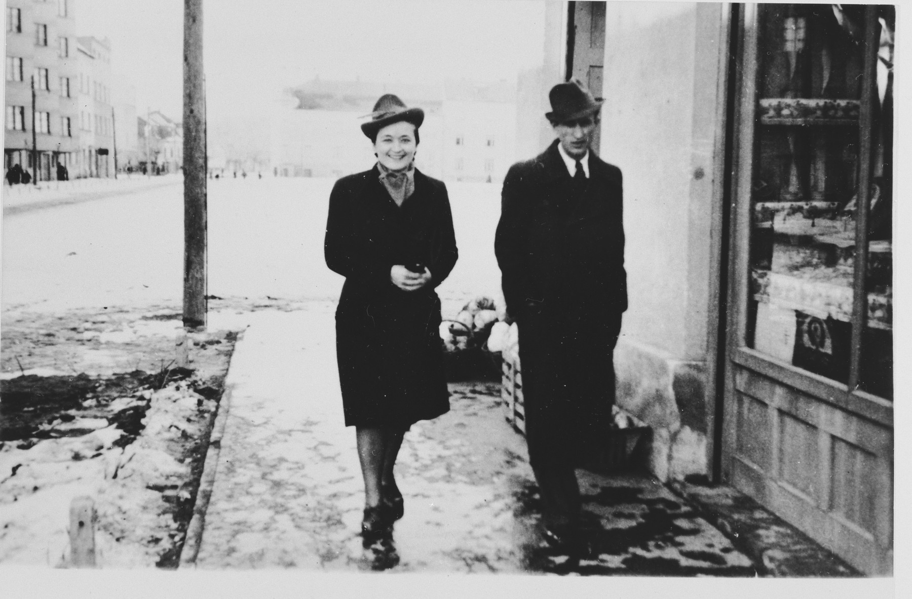 A couple walks down a street in Novi Sad, Yugoslavia.  Pictured at left is Bosiljka Kapor, who joined the Yugoslav partisans in 1941.  On June 27, 1942 she was deported to Jasenovac, where she was killed in 1944.