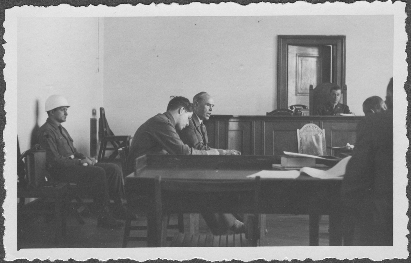 Interrogation of German Field Marshall Albert von Kesselring at the IMT Nuremberg commission hearings investigating indicted Nazi organizations.   An interpreter sits beside Kesselring and an armed guard sits behind him.  In the background is Commissioner Taylor.
