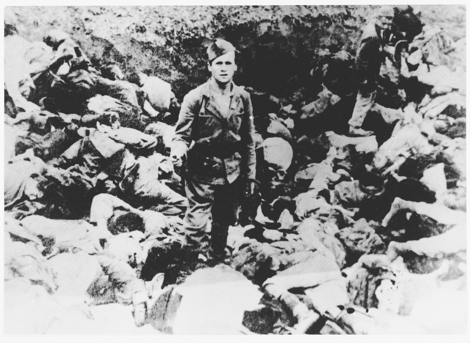 An Ustasa guard stands among the bodies of prisoners murdered in the Jasenovac concentration camp.