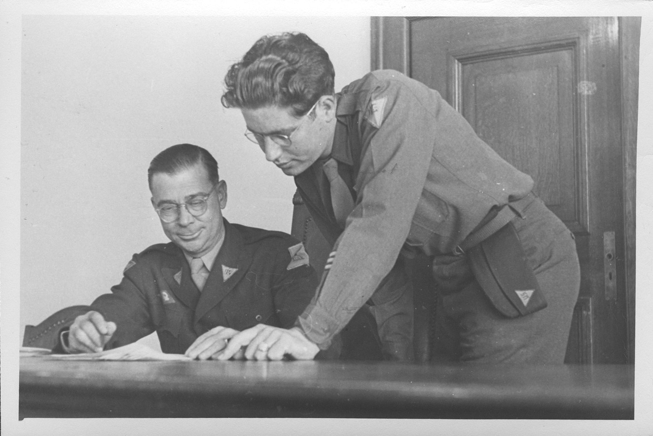 Interpreter Gerald Schwab (right) looks over a document with an unidentified commissioner at the IMT Nuremberg commission hearings investigating indicted Nazi organizations.