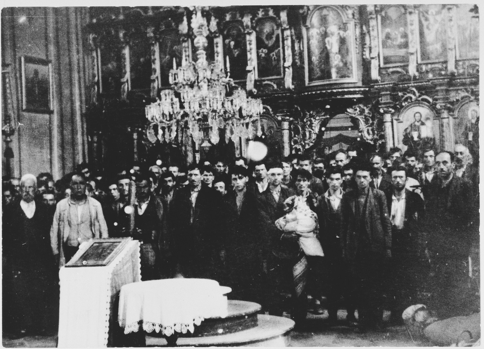 Serbian civilians who are being forced to convert to Catholicism by the Ustasa regime stand in front of a baptismal font in a church in Glina.    More than 1200 Serbs from Glina were forced to convert.  They were later slaughtered in the same church where they were converted.