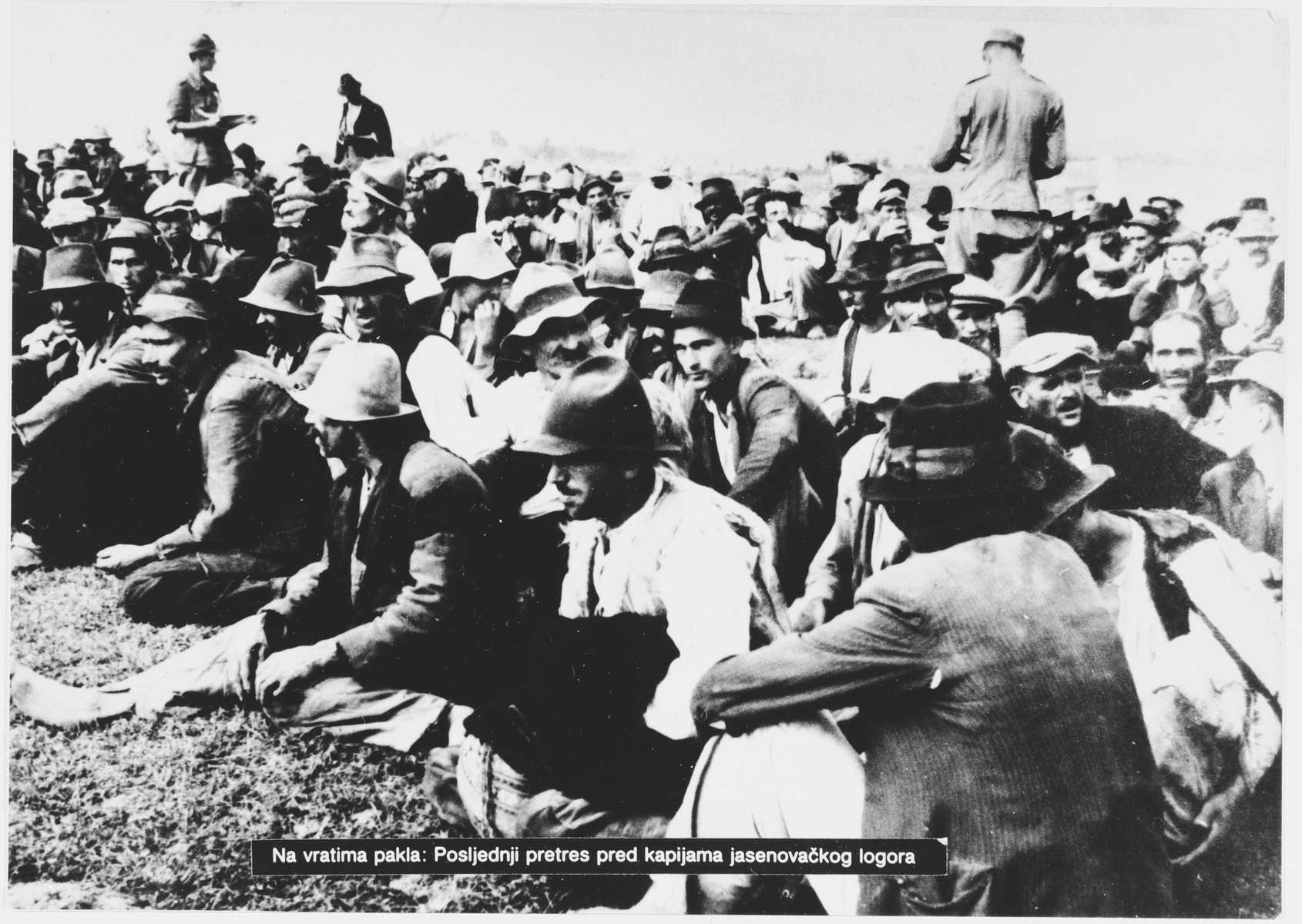 "Ustasa guards move among a large group of Serbian villagers who are seated on the ground near the entrance to the Jasenovac concentration camp.  Original caption reads, ""At Hell's door: last search at gates of camp Jasenovac"""