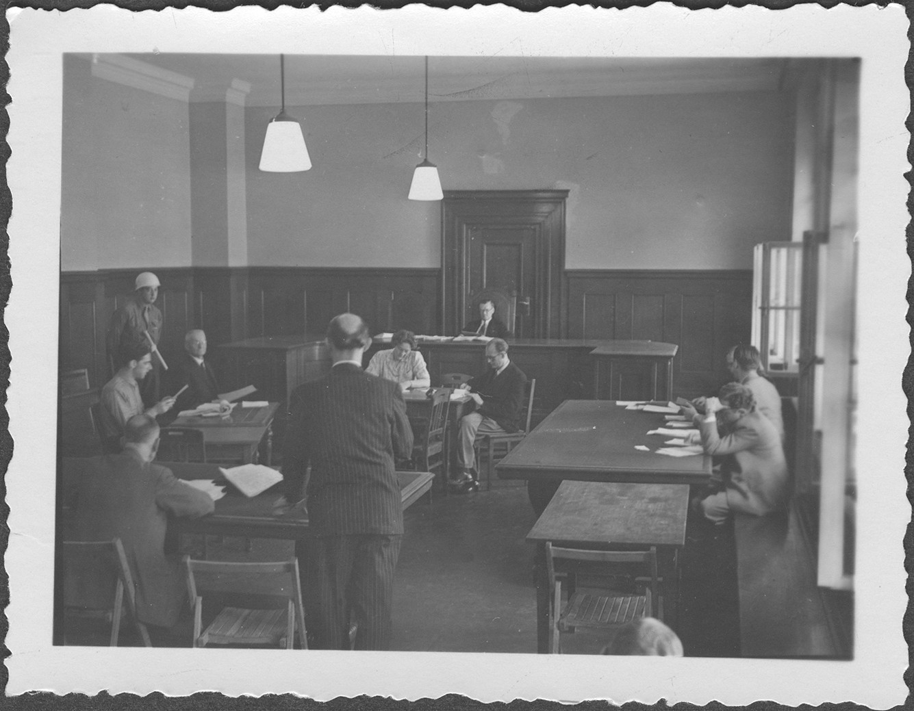 Interrogation of General Franz Halder by defense counsel Dr. Hans Laternser (standing with back to the camera) at the IMT Nuremberg commission hearings investigating indicted Nazi organizations.   Commissioner McIlwraith can be seen in the background.