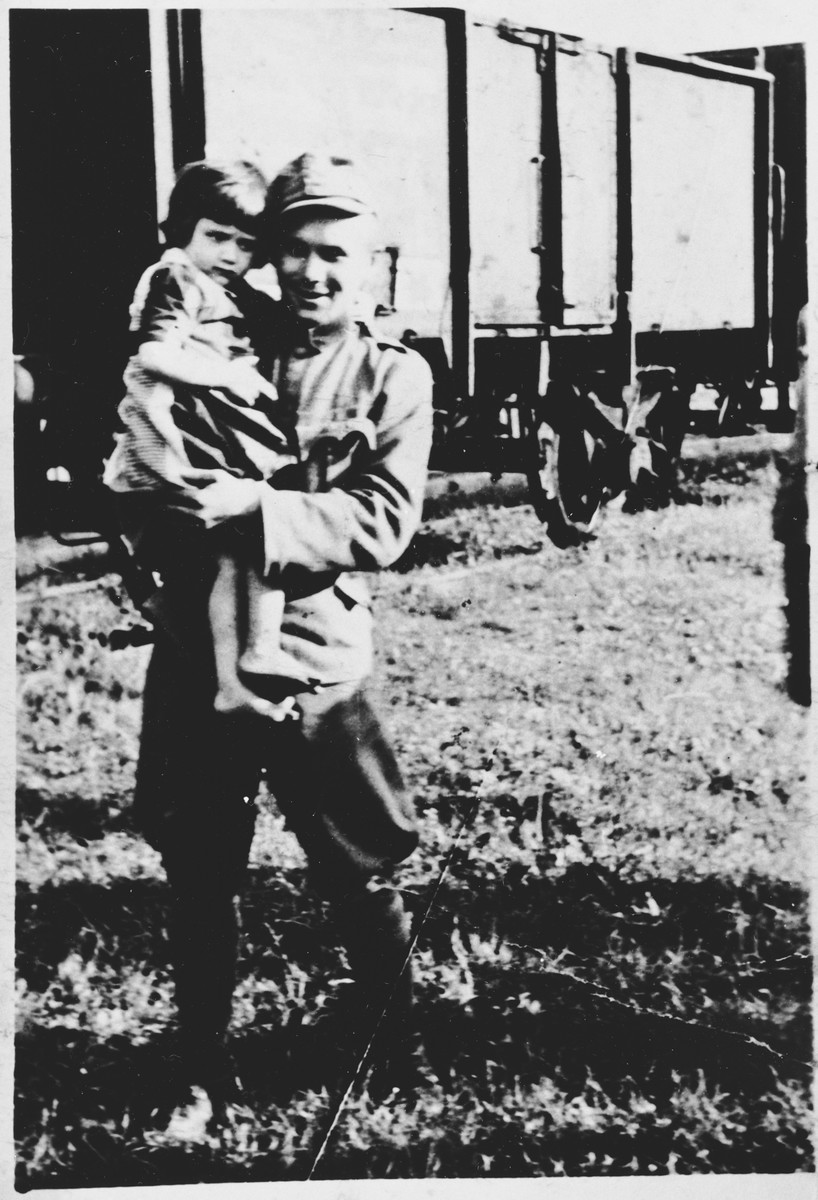 An unidentified soldier poses with a Serbian child in front of a railcar at the Pecana camp in the Sisak concentration camp for children.  The child pictured is Mara Visnjic (b. 1939) from the village of Gornje Dubrave in the Ogulin district.