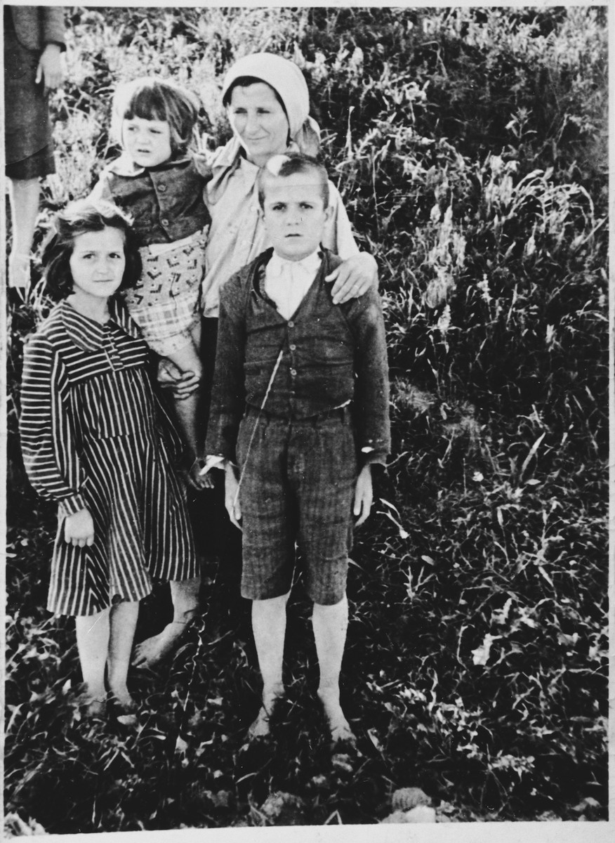 A Serbian mother poses with her three children at the Pecana camp in the Sisak concentration camp for children.  Pictured are Staka Visnjic (b. 1903) from the village of Gornje Dubrave in the Ogulin district, with her children Nikola (b. 1931), Ankica (b. 1932), and Mara (b. 1939).