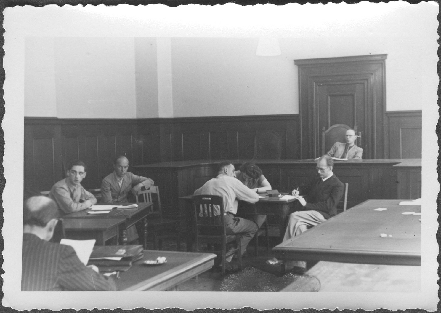 Interrogation of German General Roettiger, former chief of staff of the German 4th Army and later of Army Group Center, by defense counsel Dr. Hans Laternser (foreground) at the IMT Nuremberg commission hearings investigating indicted Nazi organizations.   Russian Commissioner I. Rasumov presides over the hearing.