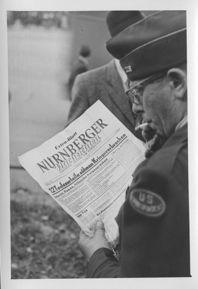 An American correspondent reads the special edition of the Nurnberger newspaper reporting on the sentences meted out by the International Military Tribunal.