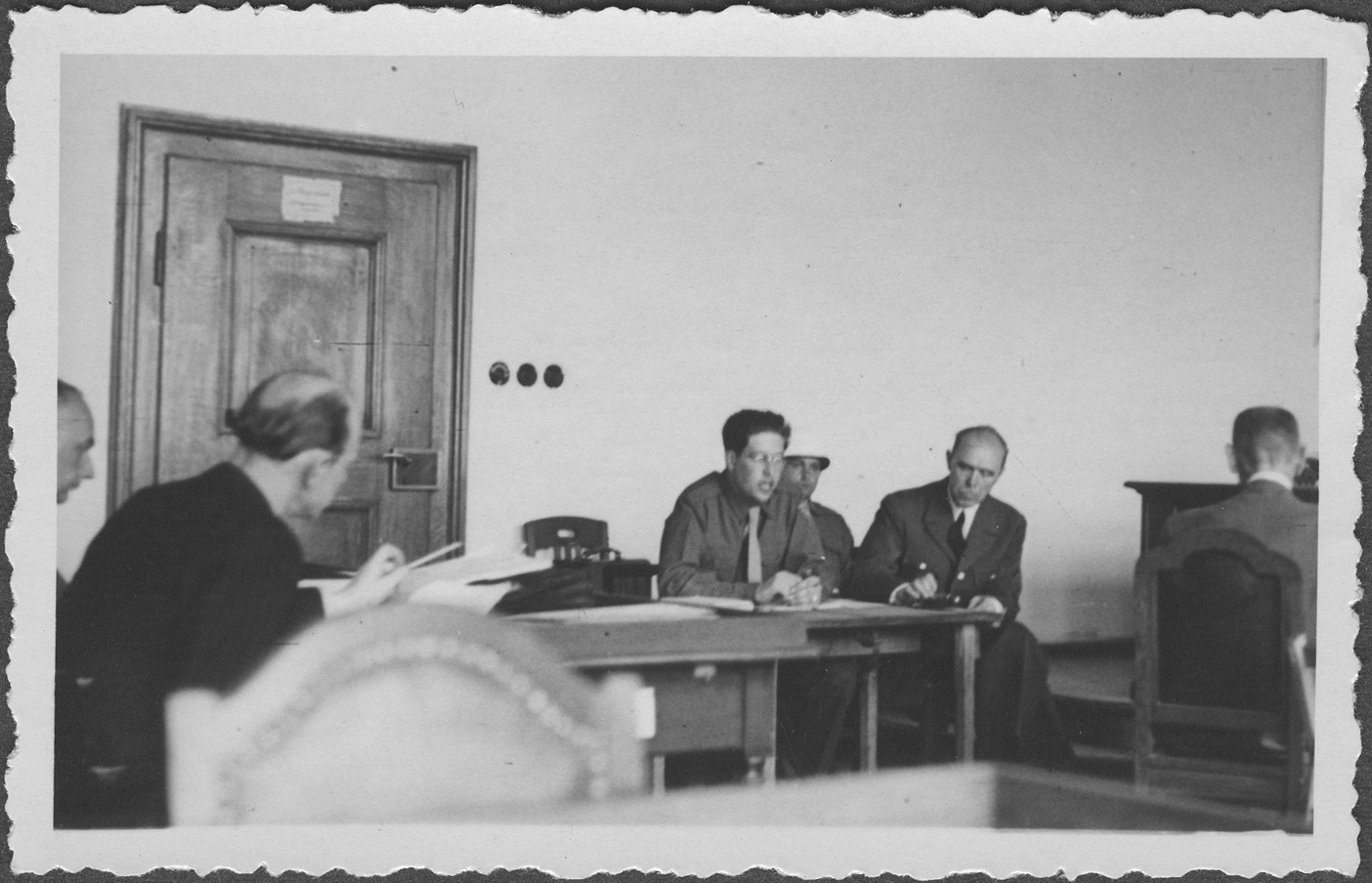 Field Marshall Albert von Kesselring testifies at the IMT Nuremberg commission hearings investigating indicted Nazi organizations.  At far left is Dr. Hans Laternser, the defense council for the Supreme Command of the Armed Forces, better known by its German initials, OKW (Oberkommando der Wehrmacht).  Fieldmarshall Kesselring sits at the table at right, next to the interpreter, Gerd Schwab.
