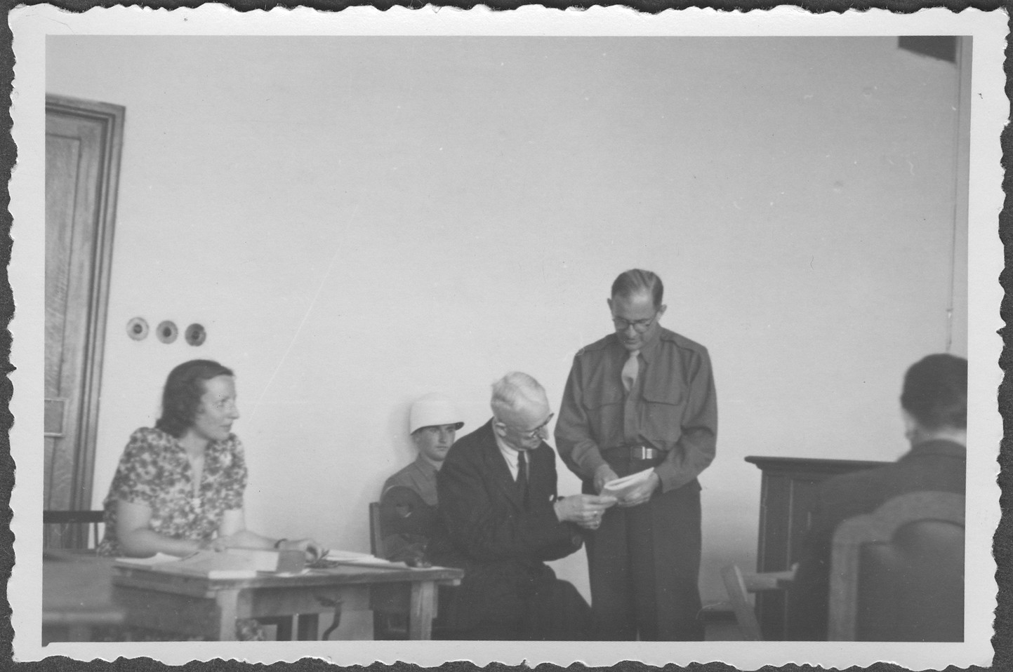 American assistant prosecutor Robert M.W. Kempner shows a document to German Field Marshall Erich von Manstein at the IMT Nuremberg commission hearings investigating indicted Nazi organizations.  Also pictured is the interpreter, Mrs. Lowenstein.