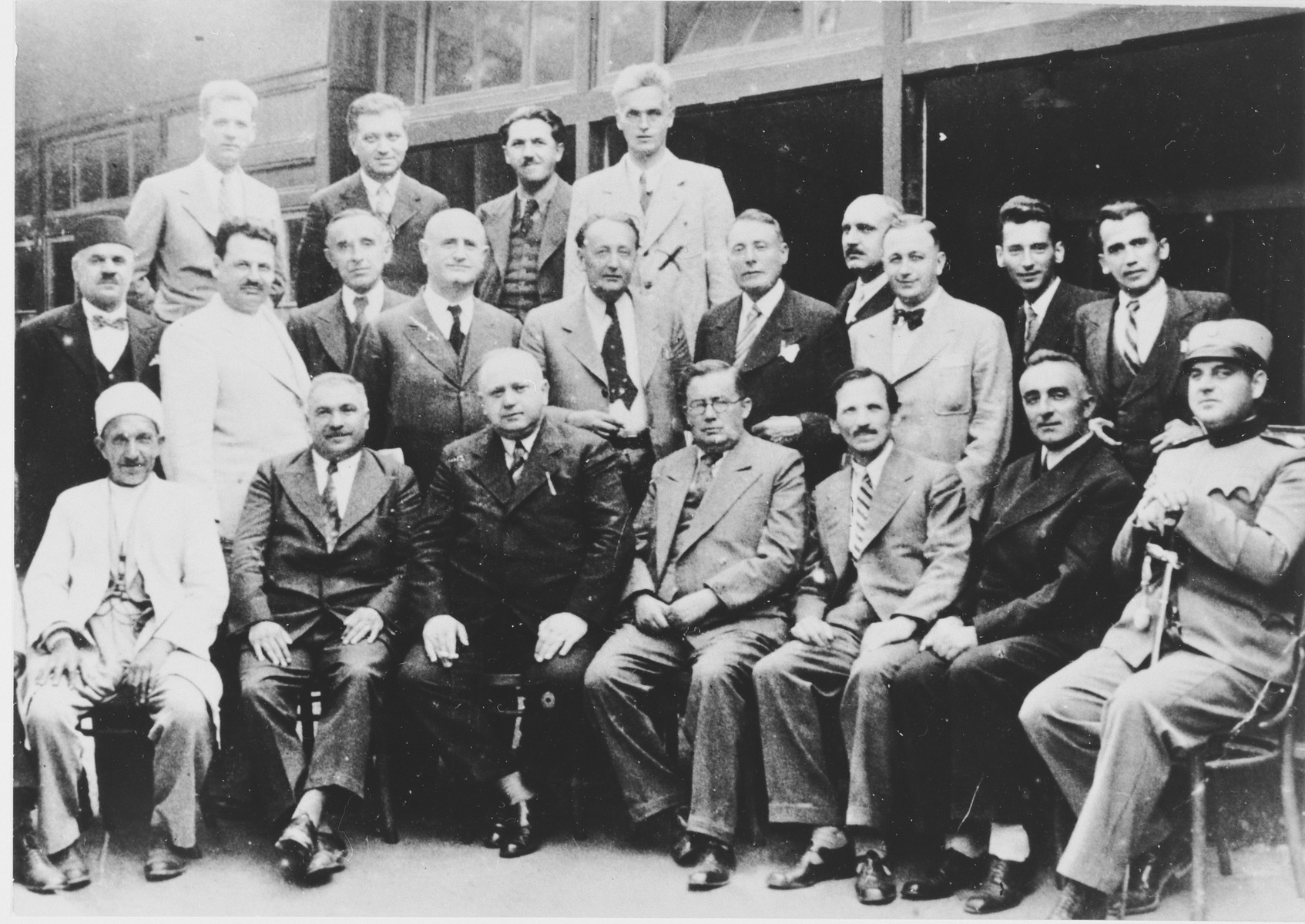 Group portrait of Yugoslav men.  Among those pictured is Mehmed Hujika (standing in the top row, right side), a teacher from Zenica and Muslim resistance fighter.  He was arrested in 1944 and taken to the Lepoglava prison, where he was killed.