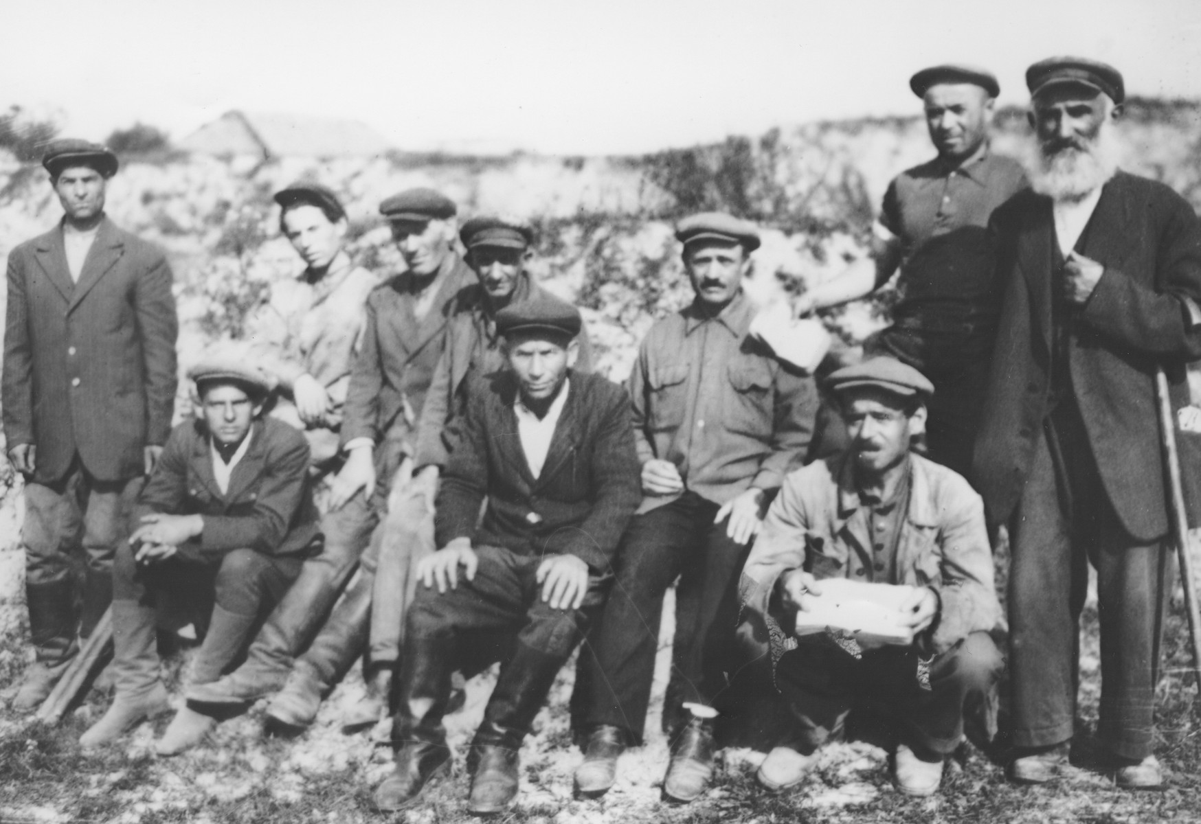 Jewish survivors pose next to a mass grave in Luboml.