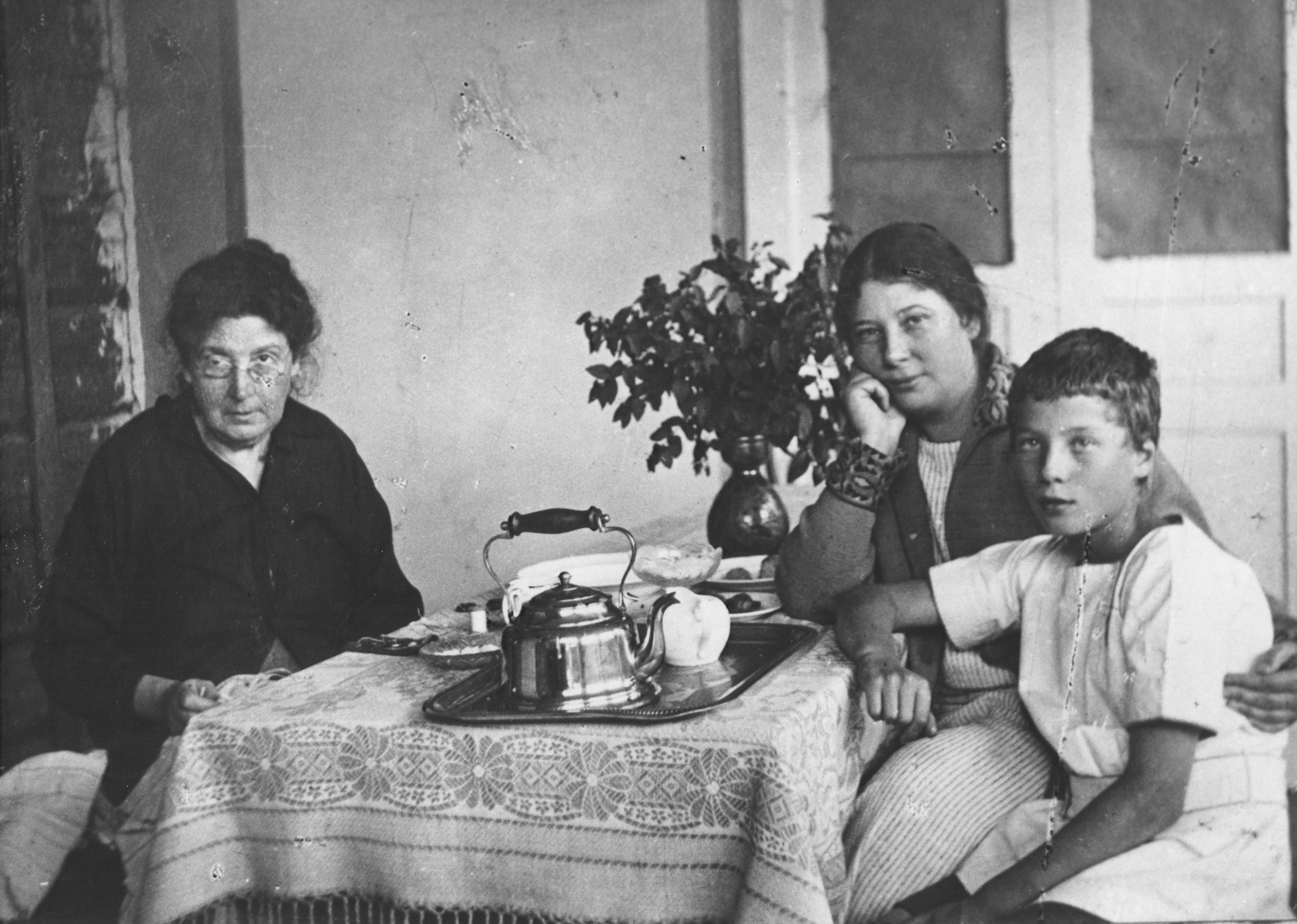 Members of the Magid family sit around a table set with a tea service.  Pictured on the left is Fanya Mikolayevsky, wife of Feodor Mikolayevsky (engraver to the Czar), with her daughter Anna Gilelevich Magid and her grandson Nathan.