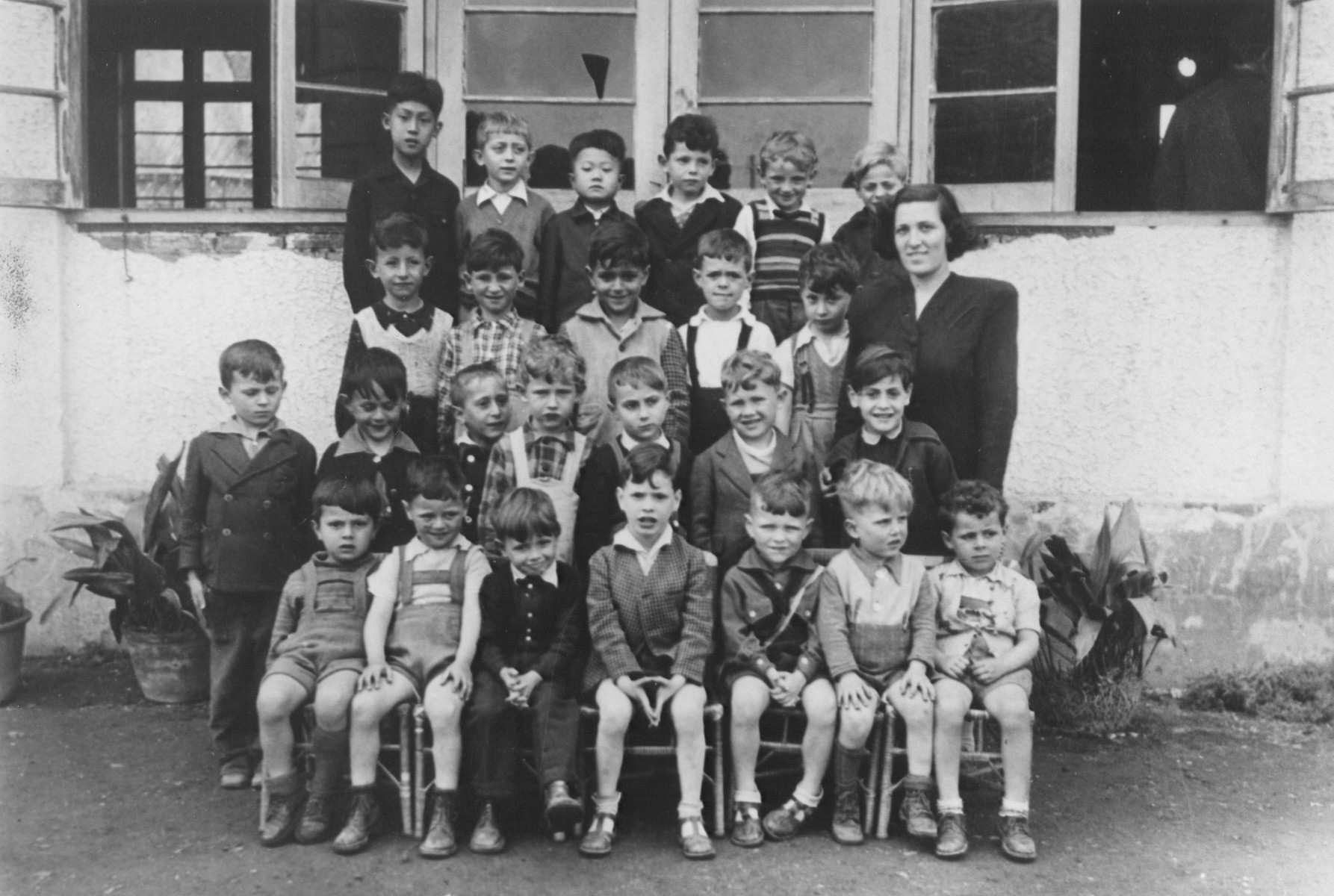 Boys in the Shanghai Jewish Youth Association.  The teacher, standing on the right, is Felicia Lewinski.  The second child from the left in the middle row is Manfred Worm.