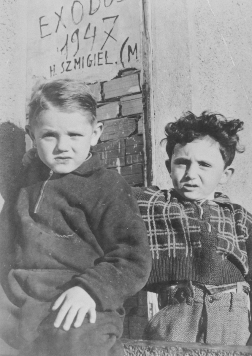 "Two young boys pose in front of a wall on which is written, ""Exodus 1947""."