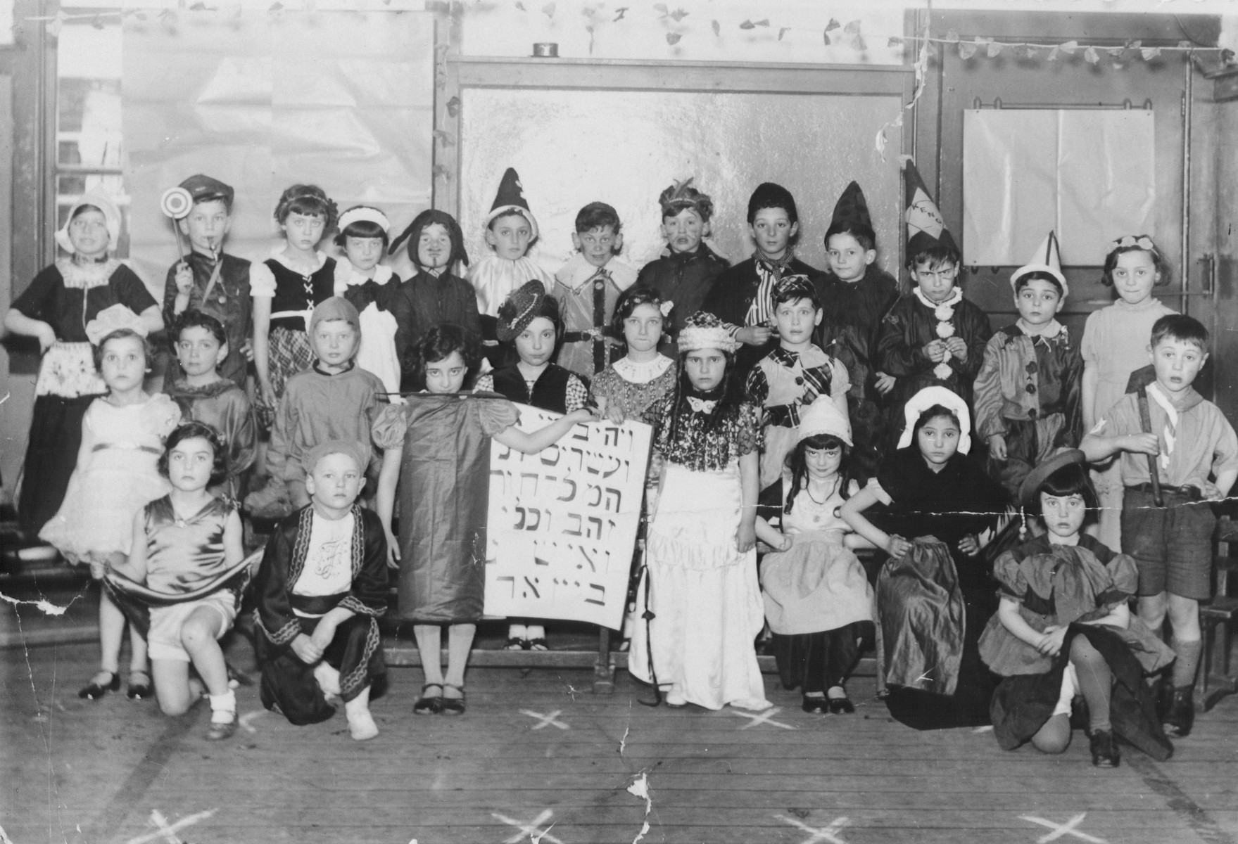 Group portrait of children in a Jewish school in Amsterdam dressed in Purim costumes.  Among those pictured is Maurice Raynor (top row, sixth from the right).