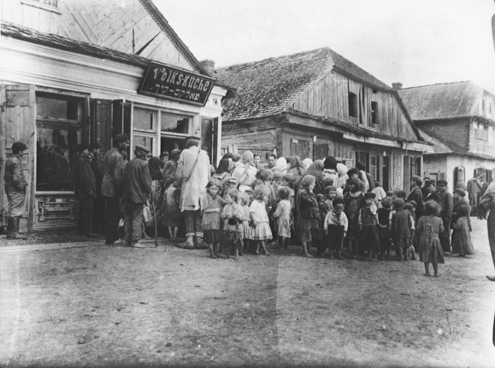 Women and children wait in line outside a soup kitchen in Luboml.