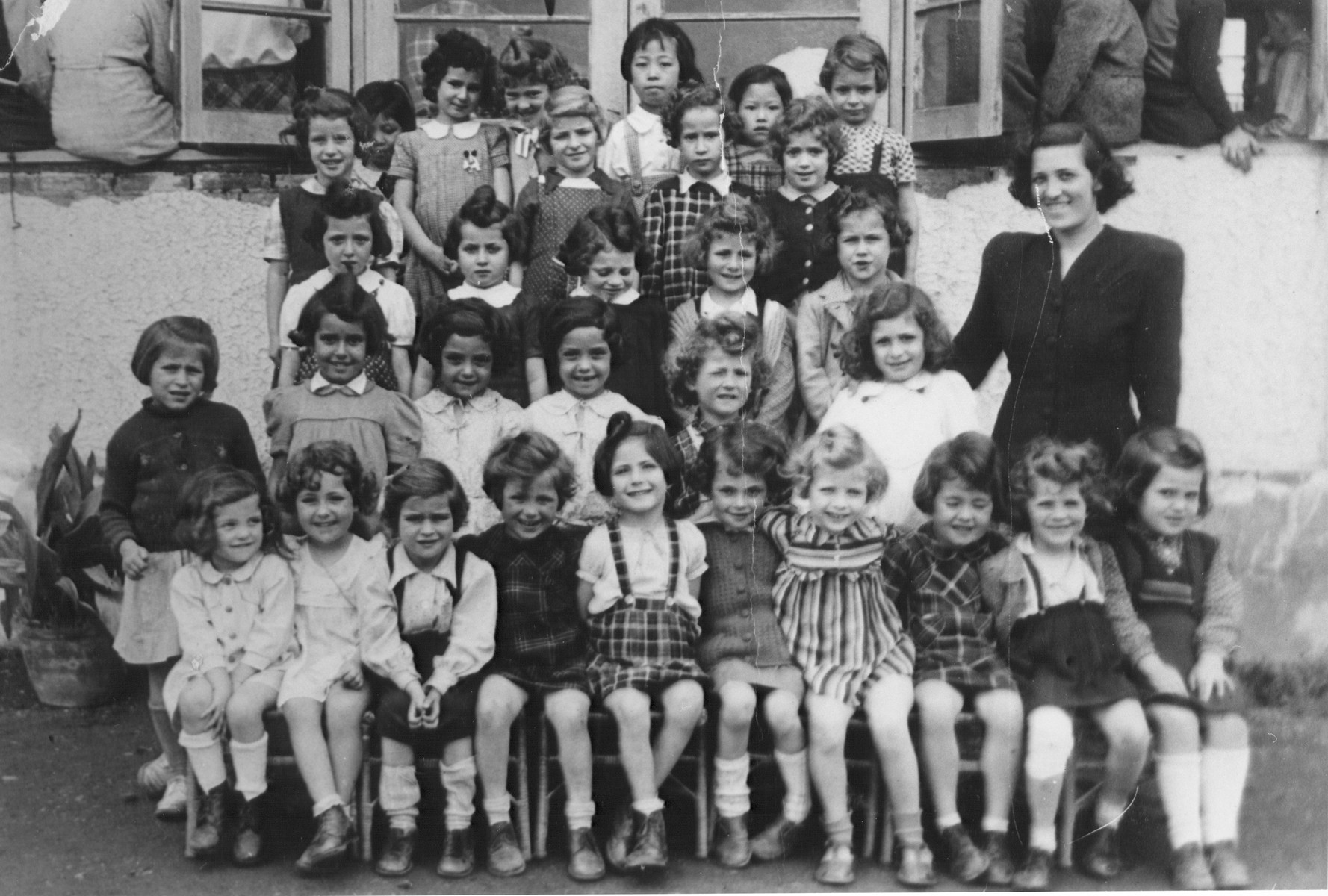 First grade class of the Kadoori School in Shanghai.  Sonja Kripps is standing on the top row at the far left.  Third row (second and third from the left) are the Bayer twins.  Naomi Strauss is second row, center.  The teacher, standing on the right, is Felicia Lewinski.