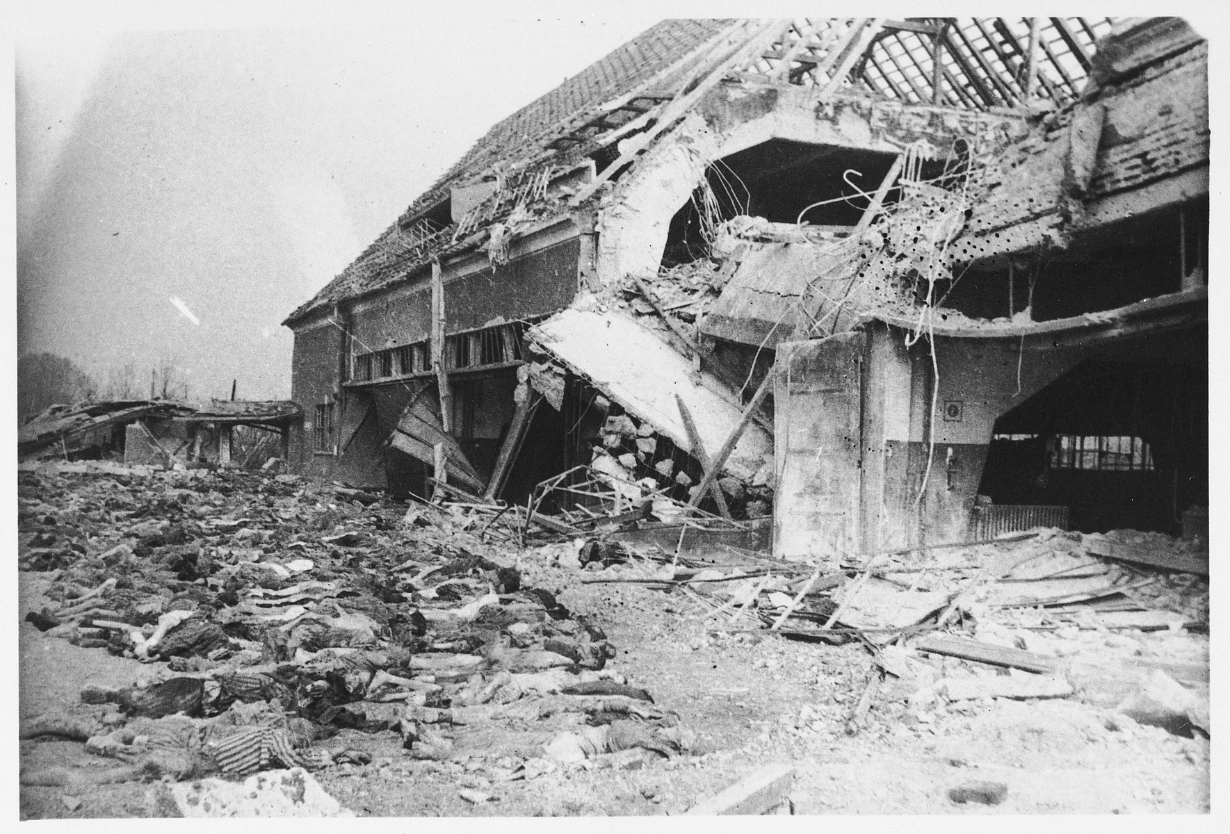 View of bodies of victims lying in front of a destroyed building in the Nordhausen concentration camp.