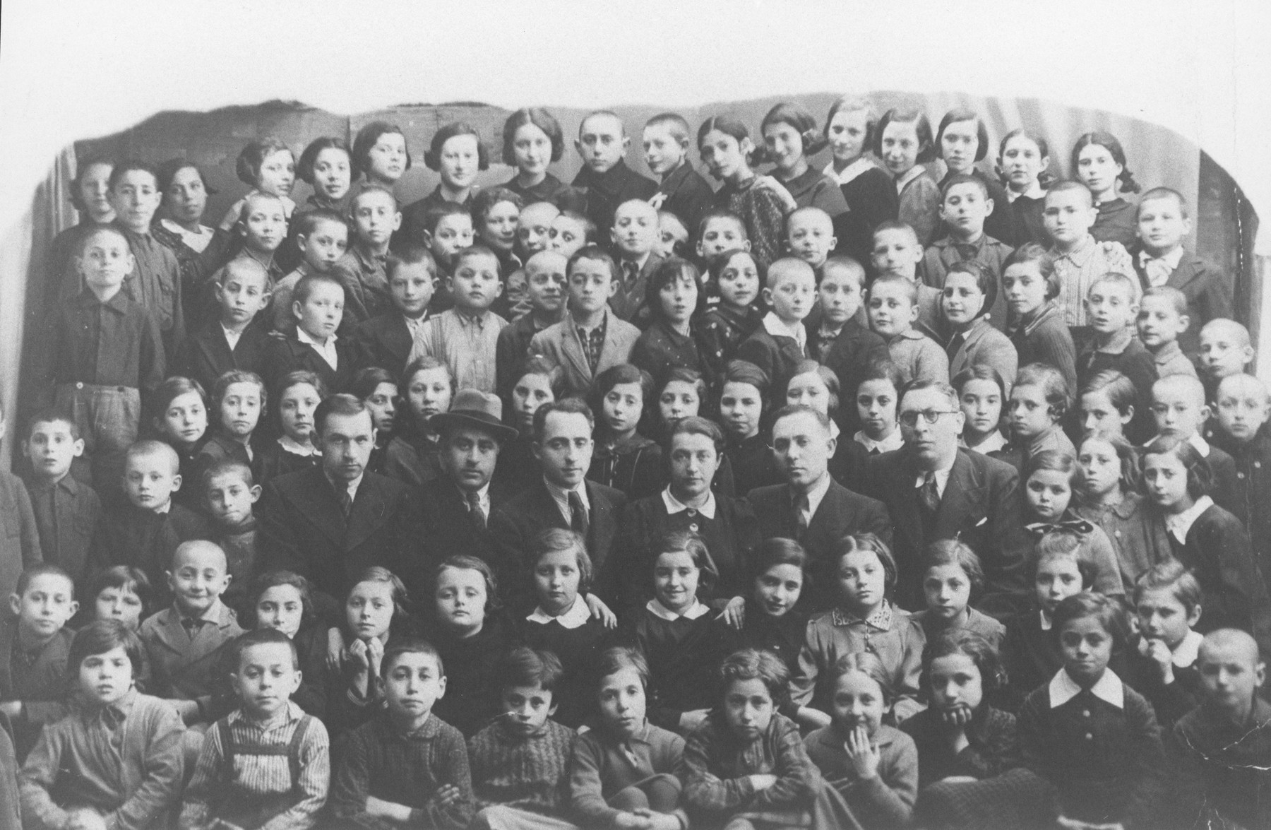 Group portrait of students and teachers in a Jewish school in Telsiai, Lithuania.  The man in the fedora, Rabbi Fivel Krubelnik, was the last head of the Telshe Yeshiva.