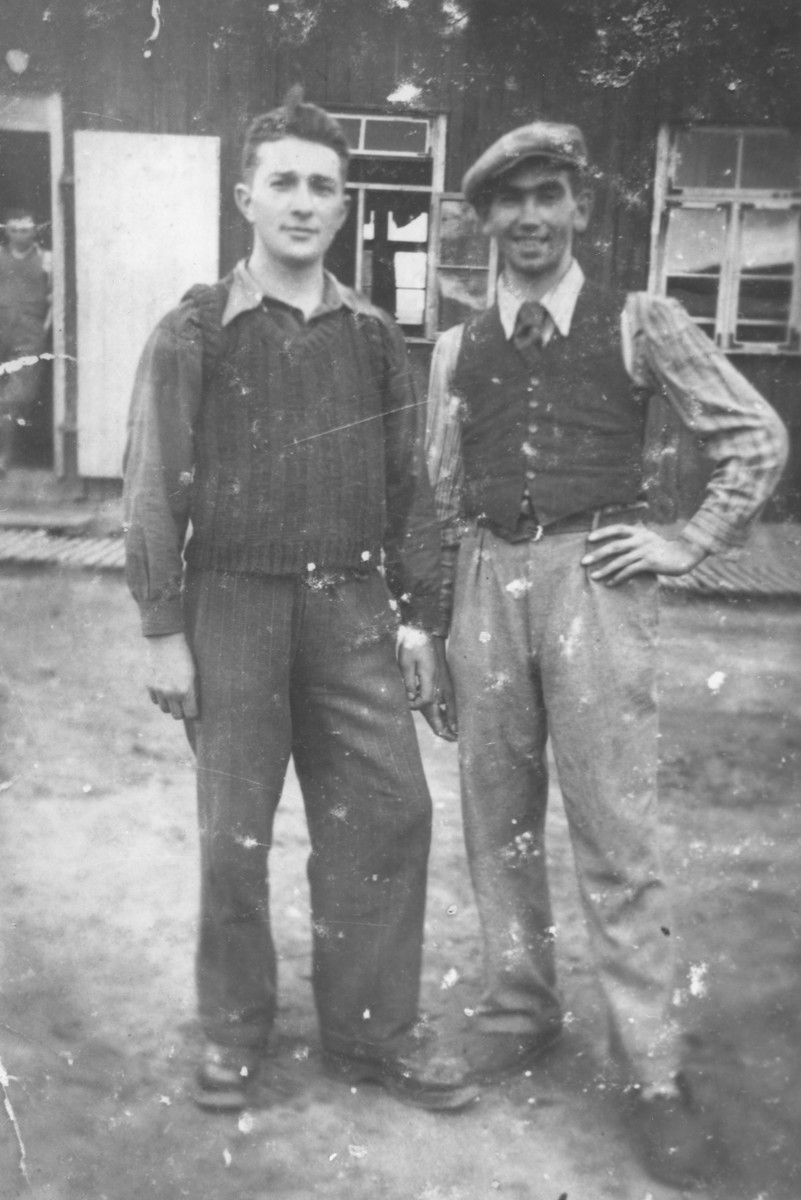 Two Jewish youth pose outside a barracks in the Sdroin labor camp near Ozorkow.  Pictured from left to right are Ignatz Kurek and Jankl Moshe Gornicki.  Gornicki perished in Riga.