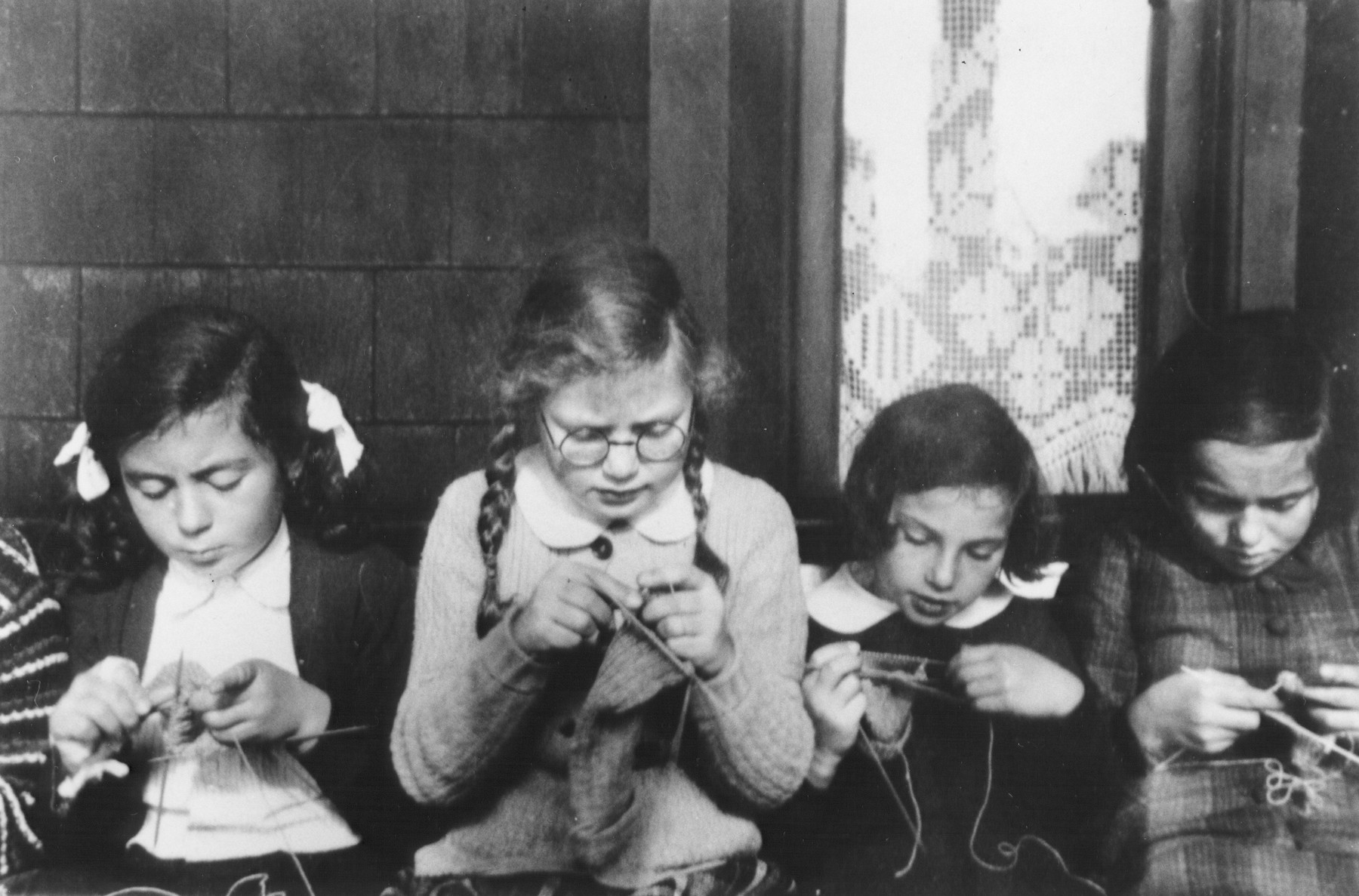 Jewish refugee children knit for the war effort in the Larino home in Balwyn, outside of Melbourne.  Pictured left to right are Margot Goldstein, Jo Lehmann, Ellen Rothschild and Ellen Lewinski.  The home was sponsored by the Jewish Welfare Society.