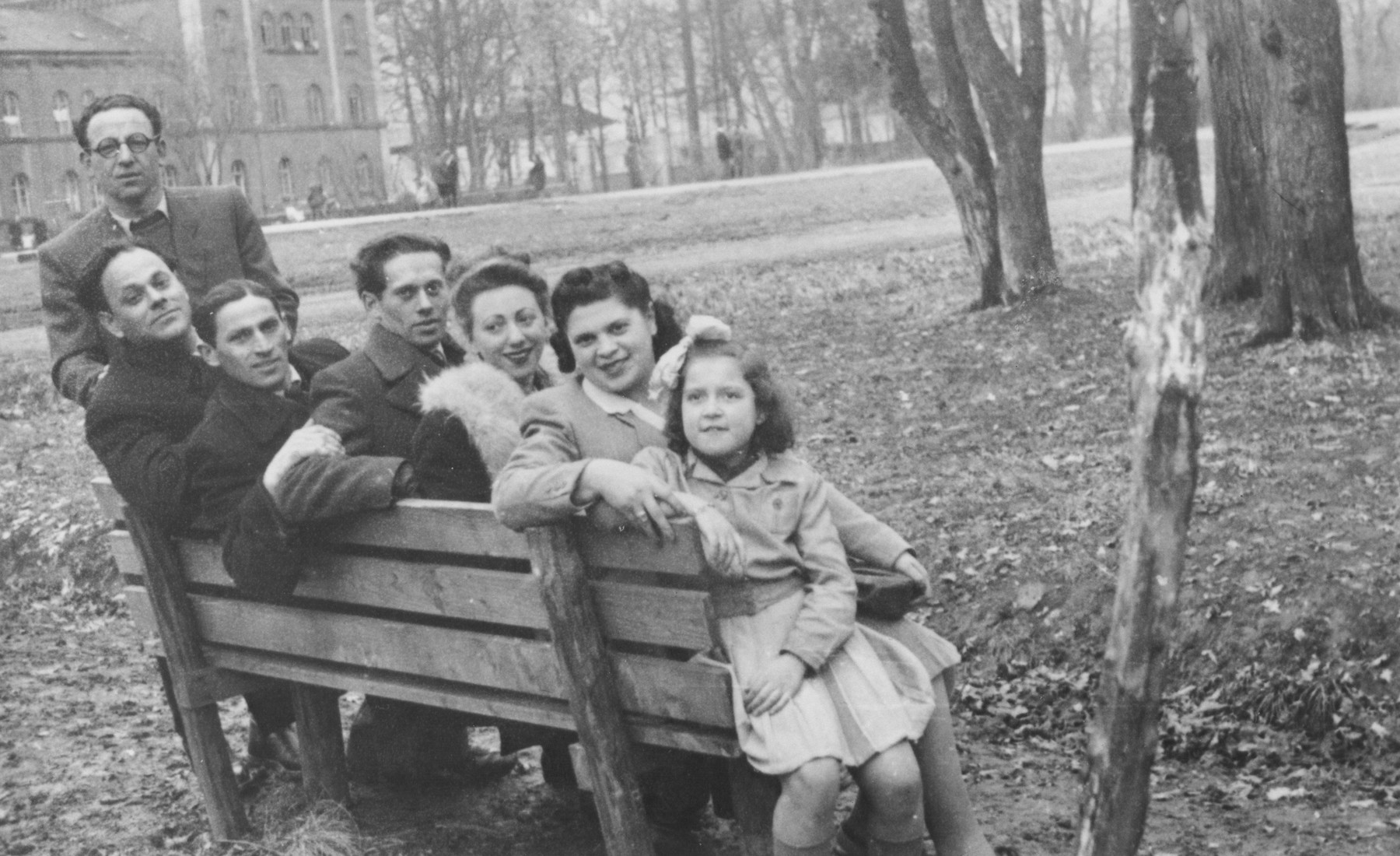 A group of Jewish displaced persons sits on a park bench in Munich.  From left to right are Blumenthal, Pesach Gutmark, David Rogow, Norbert Horowitz, Mrs. Blumenthal and Rita Karpinovitch.
