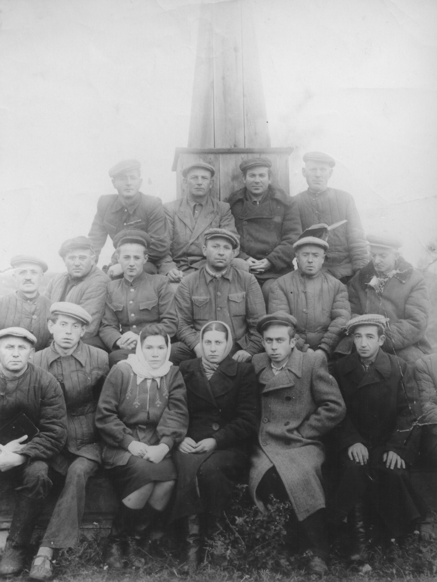 A group of survivors pose in front of a monument which they are constructing in memory of the Holocaust victims of Luboml.