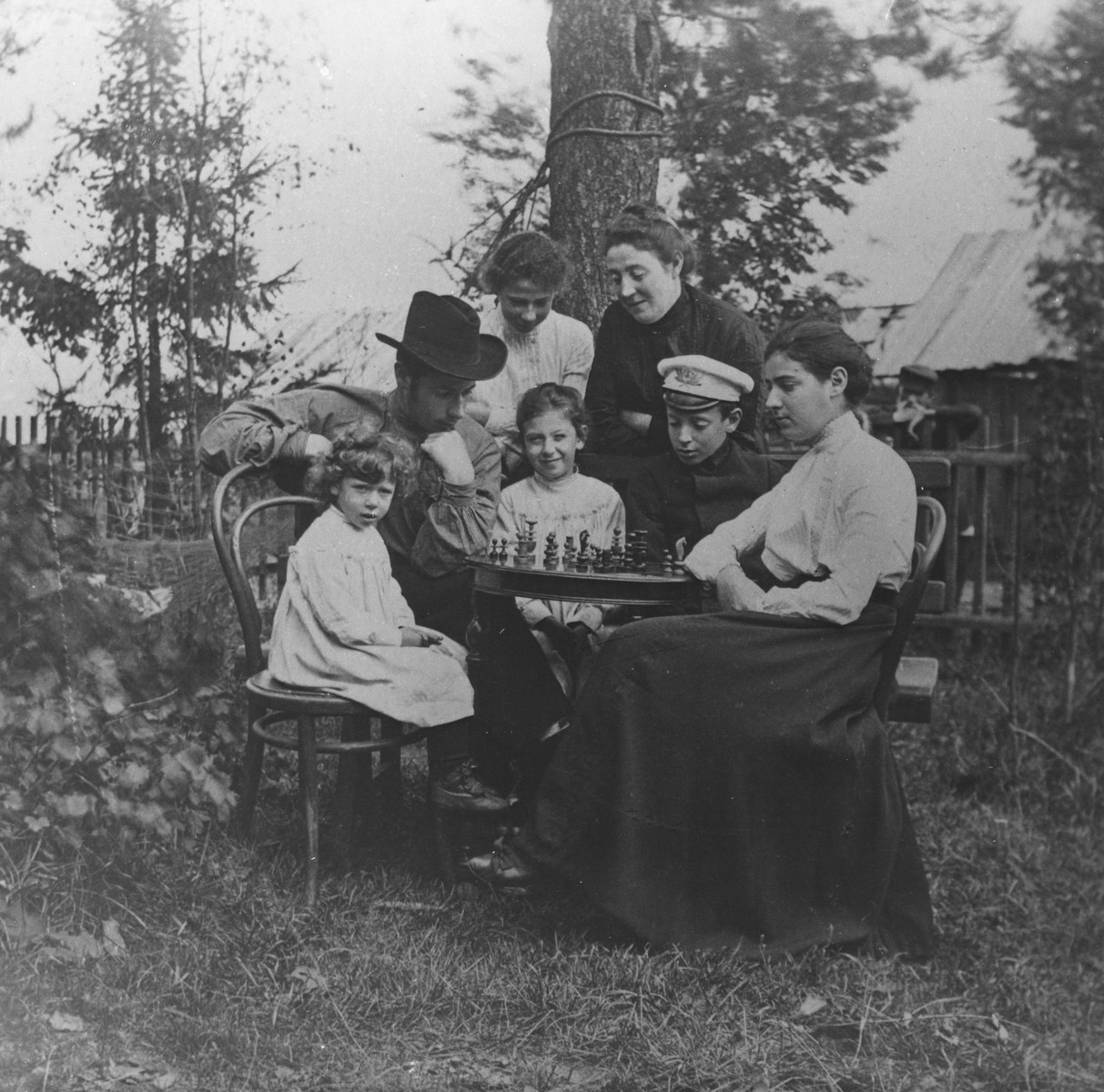 Members of the Michaelevsky family play chess outside in the yard of their home in Petrograd, Russia.