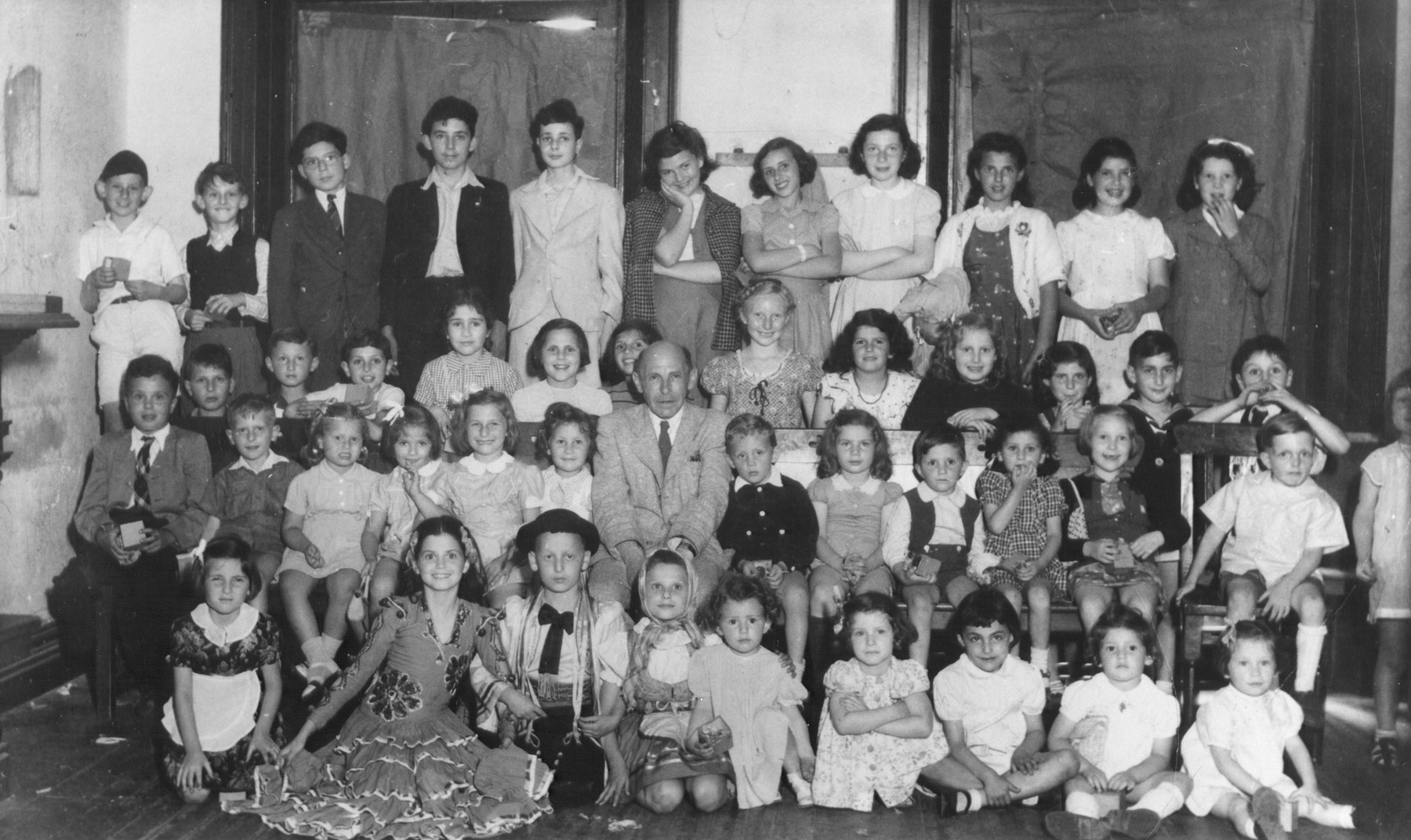 Group portrait of children, some of whom are in costume, in Shanghai.  Those pictured in the front row include Elisabeth Gauglberger (far left), Liane Poutau (second from left) and Sonja Krips (sixth from left).