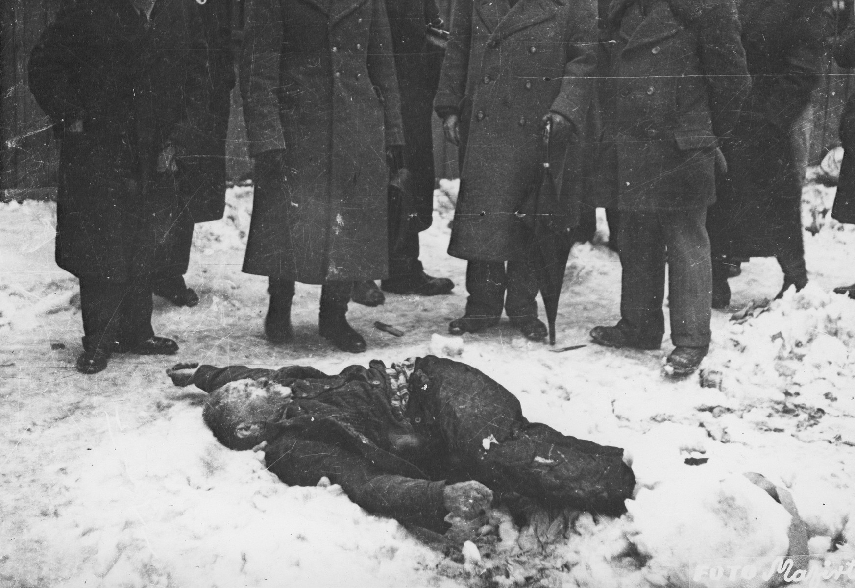 "Members of the Commission for the Investigation of Nazi and Arrow Cross Atrocities examine the body of a Jewish man killed in the Budapest ghetto.  During the last few months of the war in Hungary, the Nyilas (Arrow Cross) exploited the anarchic conditions in the areas still under their control to continue their excesses against the Jews.  This was particularly true in Budapest, despite the fact that the Soviet army had completely encircled the city by December 27, 1944.  The reign of terror that had begun with Szalaszi's assumption of power on October 15, 1944, went almost completely unchecked after the beginning of the Soviet siege on December 9.  Gangs of armed Nyilas--mostly teenagers--roamed the city hunting for Jews in hiding.  They searched them out in hospitals, shelters, homes outside the ghetto, in the International Ghetto, and in the large ghetto.  After robbing the Jews of their remaining valuables, the Nyilas shot them on the spot or marched them to the banks of the Danube, where they shot them, and threw their bodies into the river.  A large number of Jews who were murdered in the ghetto were buried in mass graves in the courtyard of the Dohany Street Synagogue.  The most horrific of these attacks occurred on the Pest side of the capital, at the two Jewish hospitals located on Maros and Varosmajor streets.  The Maros Street hospital, which had operated under the protection of the International Red Cross during the German occupation, was attacked on January 11, 1945.  After the initial melee, during which Nyilas gang members wantonly destroyed hospital equipment, threw patients out of their beds and trampled them, and murdered staff members, survivors were ordered to dig a mass grave, remove and bury the bodies.  They were then shot and buried in the grave themselves.  Only one nurse survived of the 92 people that were in the hospital at the time.  Three days later, on January 14, the hospital on Varosmajor Street was attacked, resulting in the deaths of 150 patients and medical staff.  These manhunts and massacres continued unabated until the liberation of Budapest in April.  [R. Braham, ""The Politics of Genocide,"" vol. 2: 995-1007]"