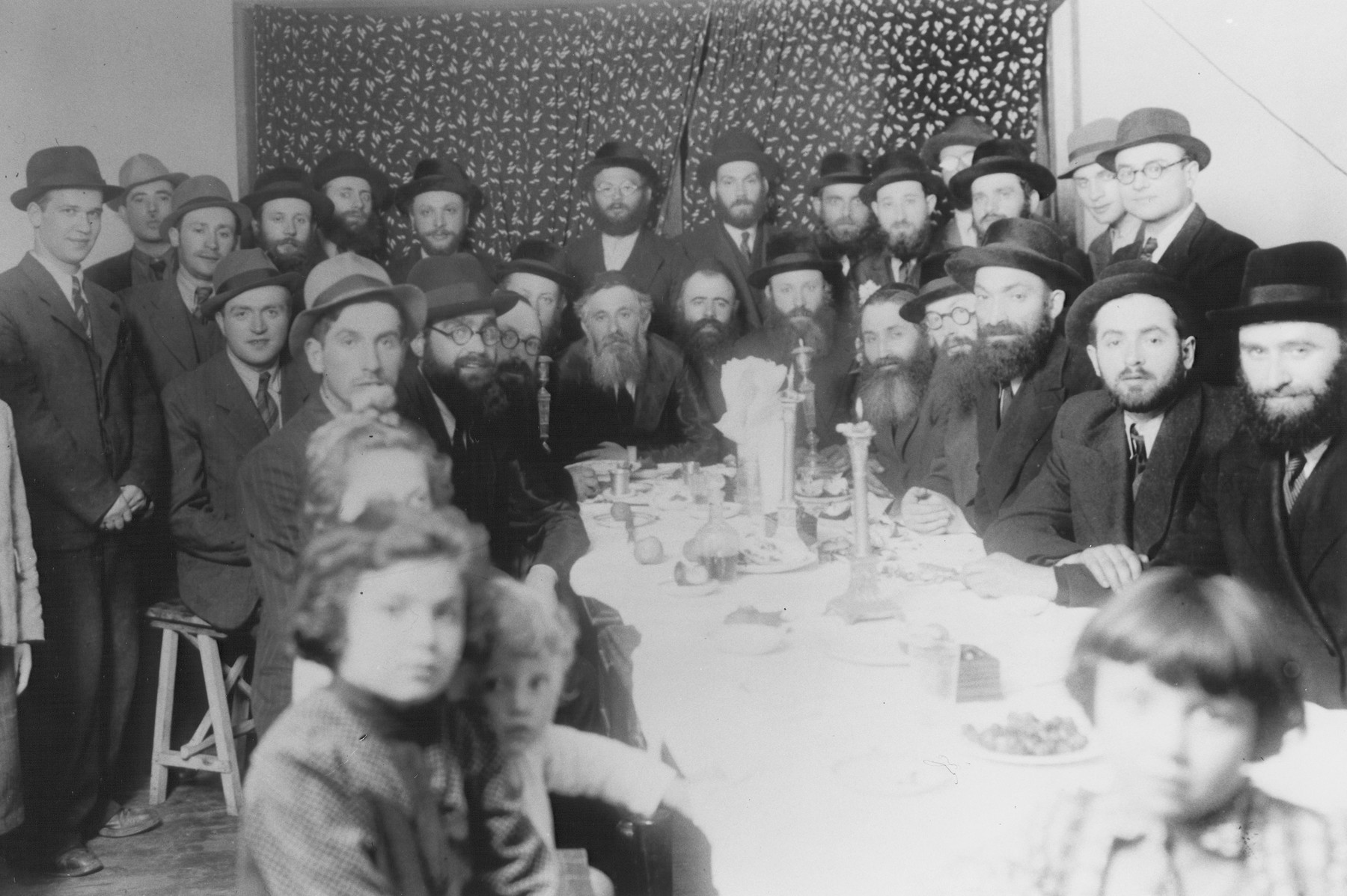 Group portrait of religious Jewish refugees from Poland at a dinner in Shanghai.  Among those pictured are Rabbi Walkin and his daughters.