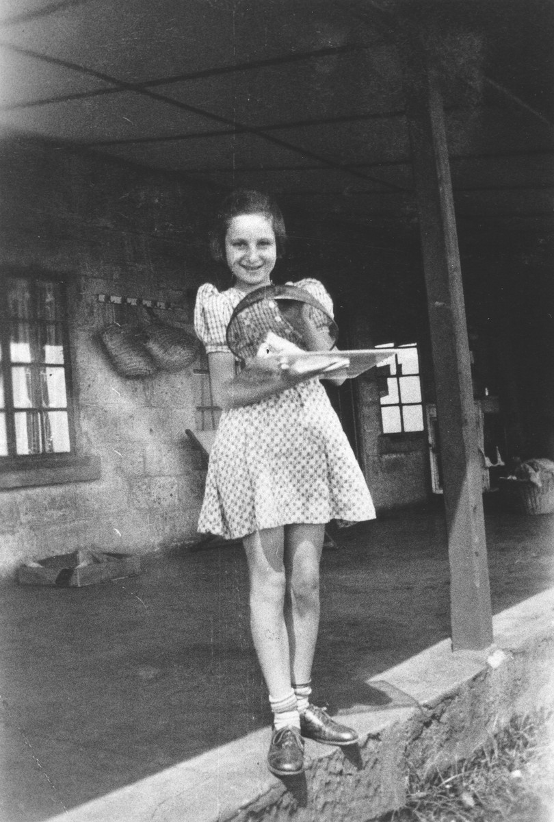 A young Jewish refugee girl stands in front of her farmhouse near Limuru, Kenya (Kiambu district), holding a cage of parakeets.  Pictured is Gisela Berg.