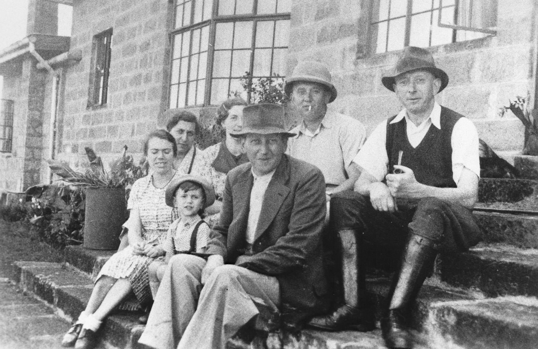 Group portrait of members of the extended Berg family outside their home near Limuru, Kenya (Kiambu district), where they found refuge during World War II.  Pictured in the front row are Rosel and Karl Berg with their son Egon between them.  Seated in the back row, from left to right, are Sara, Else, Ernest and Josef Berg.