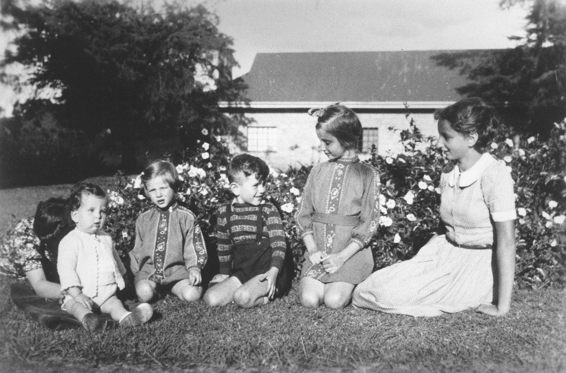 Five Jewish refugee children pose outside on the lawn of their farm near Limuru, Kenya (Kiambu district), where they found refuge during World War II.  Pictured from left to right are Philip Berg (being supported by his Aunt Erna), Hannah Baum, Egon, Gisela and Inge Berg.