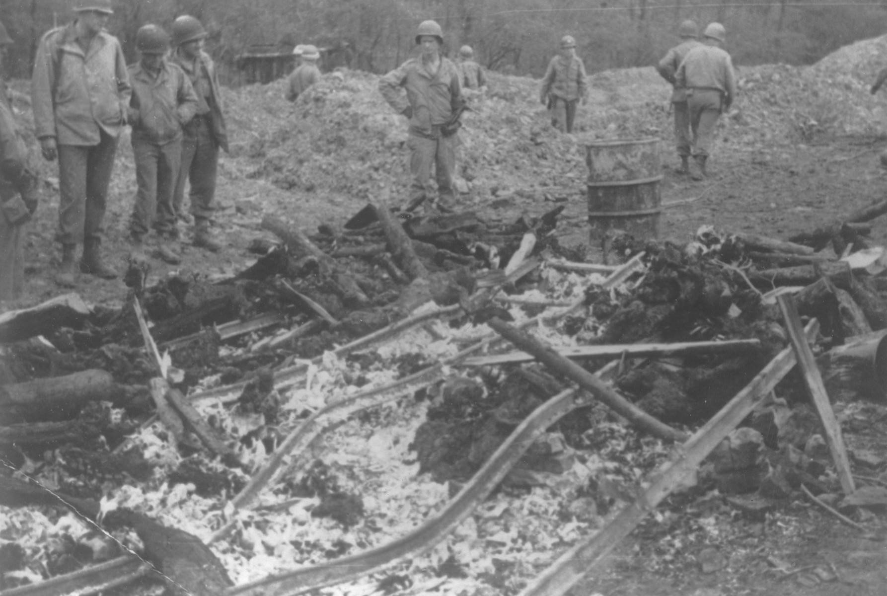 American soldiers on an inspection tour of the Ohrdruf concentration camp examine the remains of a pyre used to burn corpses.
