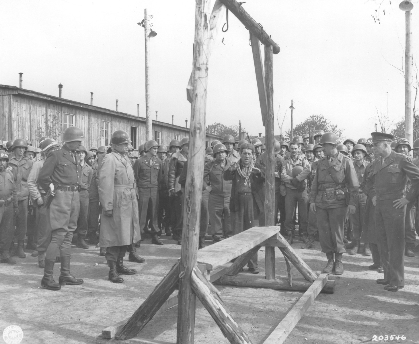 An Austrian-Jewish survivor, who had been deported from Holland, points out the gallows in Ohrdruf to General Dwight D. Eisenhower and a party of high ranking U.S. officers, including General Omar N. Bradley, Lt. Gen. George S. Patton, and Major General Troy H. Middleton, during an official tour of the newly liberated concentration camp.