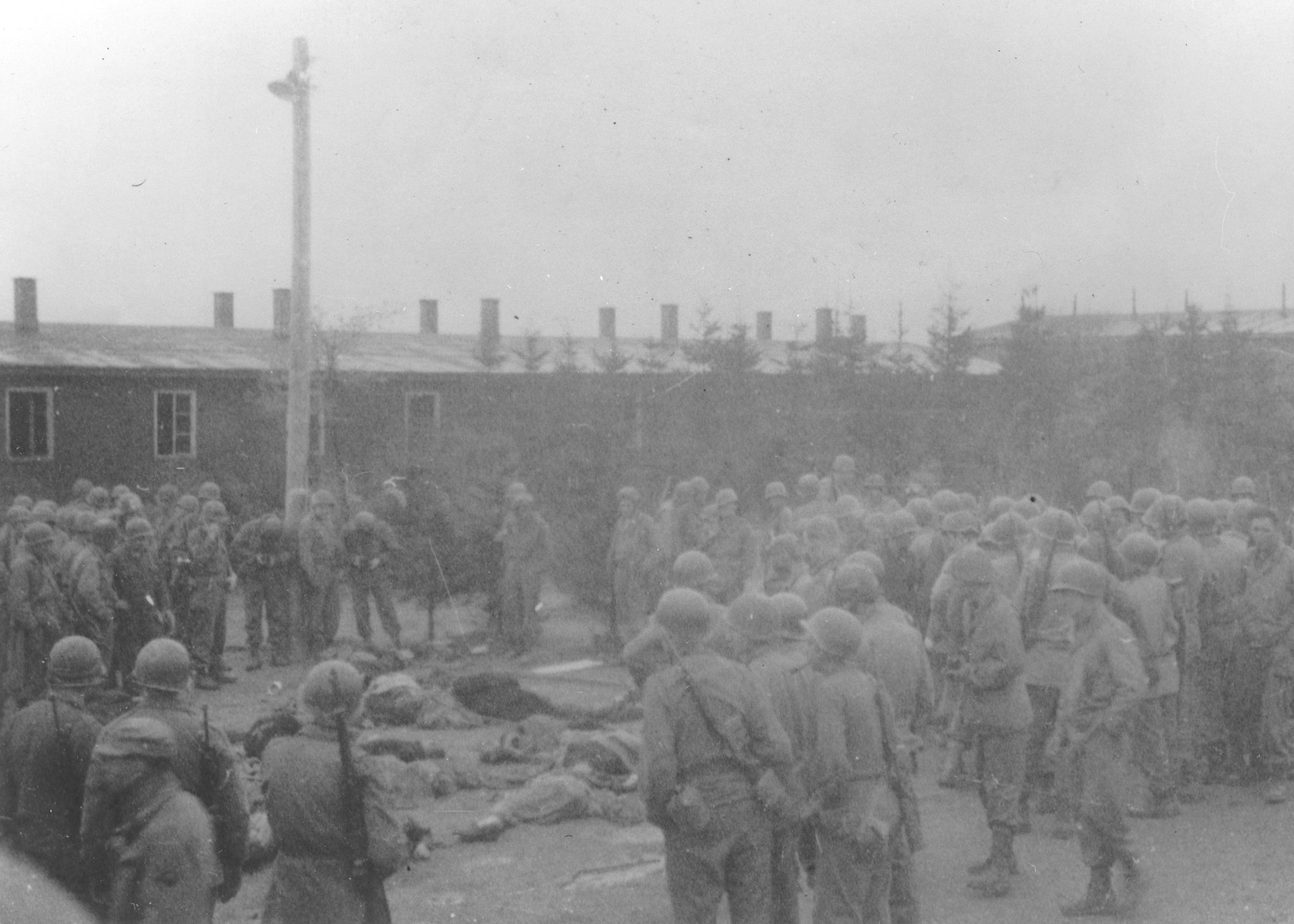 American soldiers view the bodies of Ohrdruf prisoners who were killed during the evacuation of the concentration camp.
