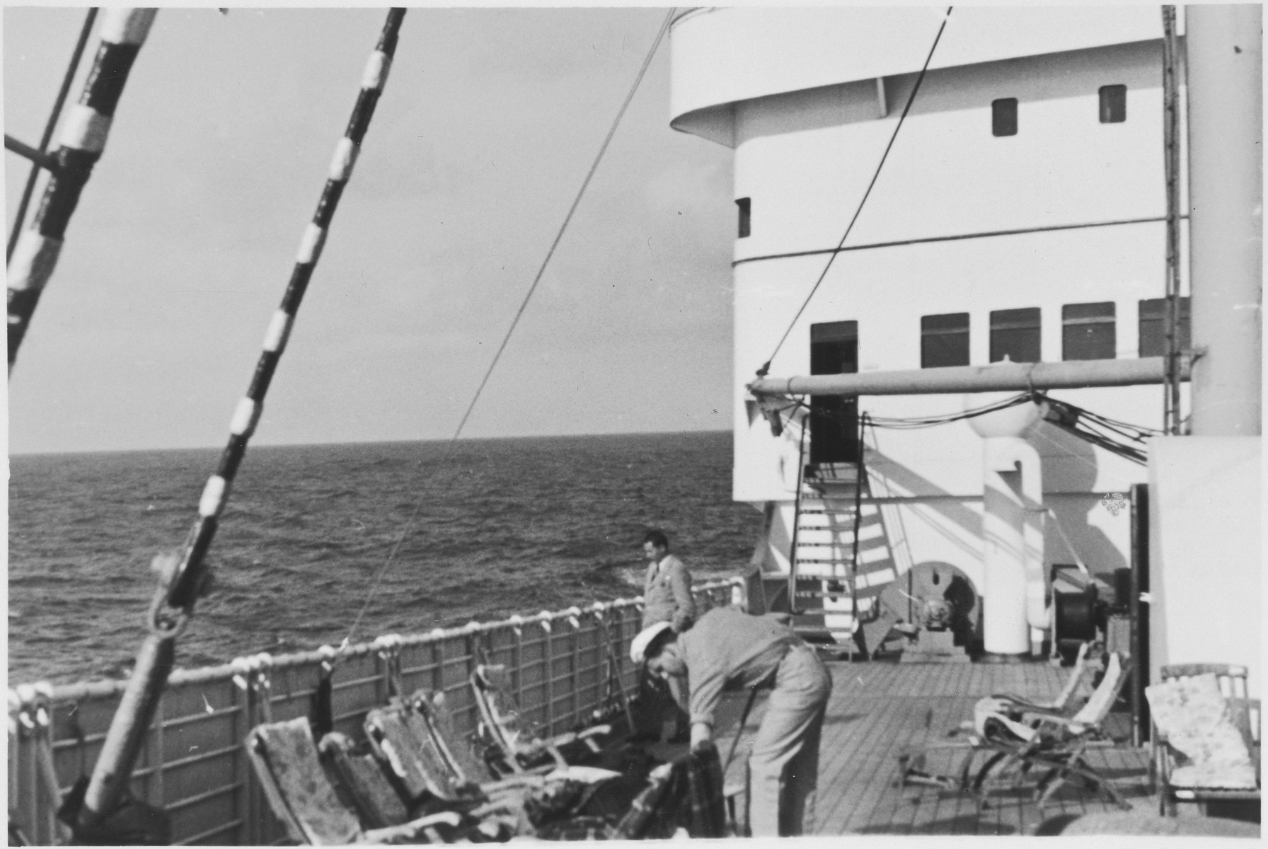 View of the bridge of the MS St. Louis.  In the foreground, a crewman cleans the deck area while a passenger standing at the railing looks out over the sea.
